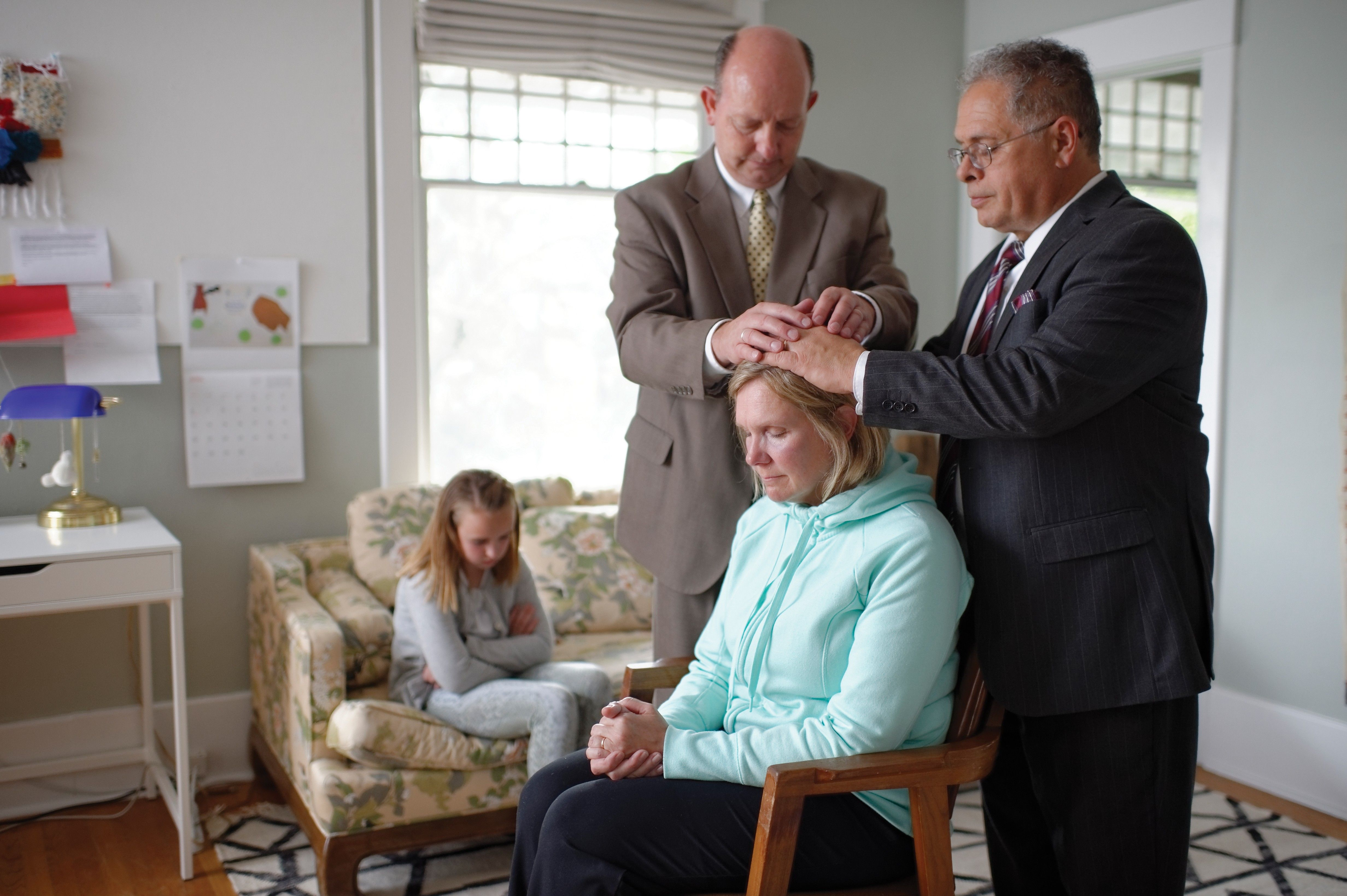 A woman receiving a priesthood blessing in her home.