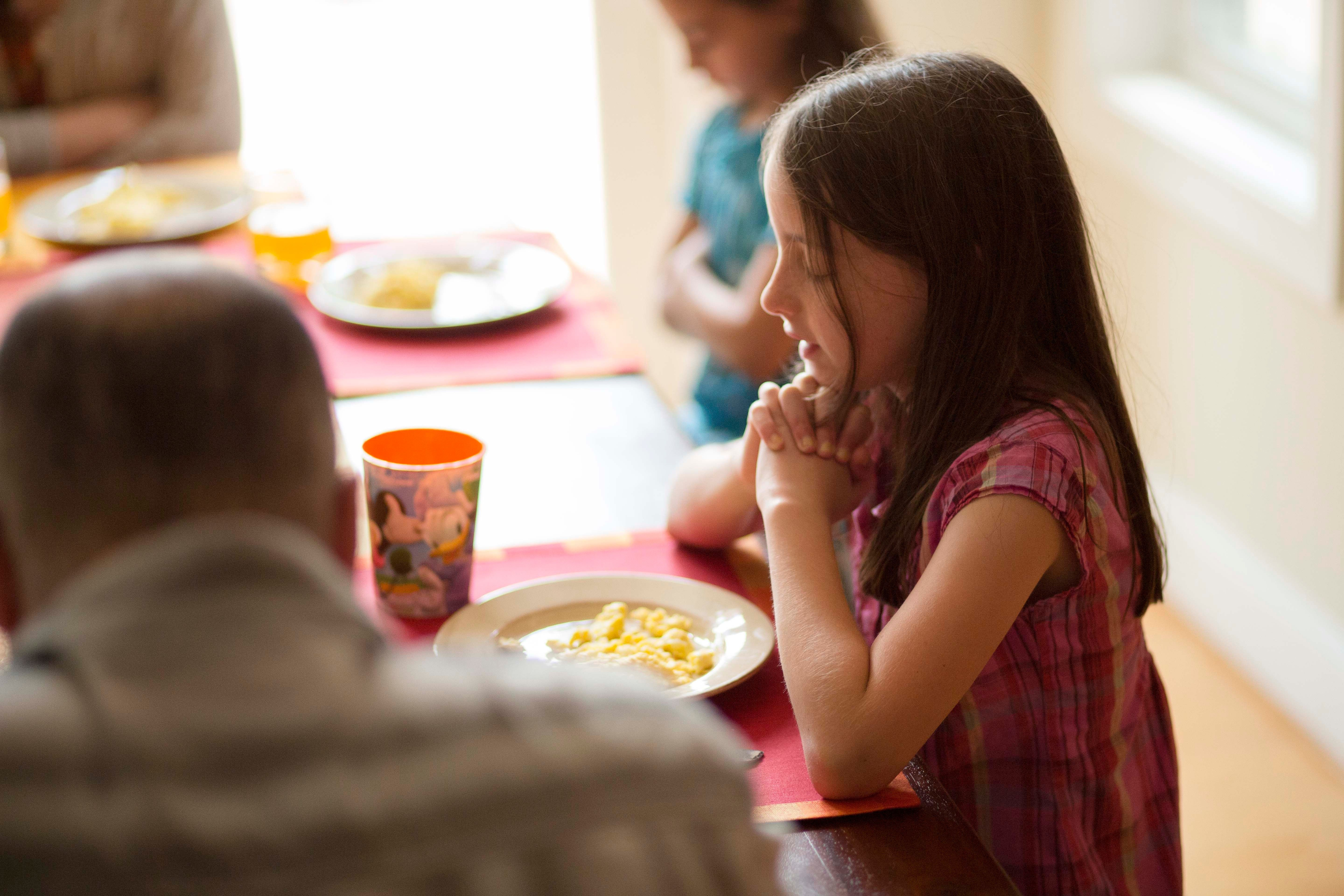 A little girl asks for a blessing on the food.