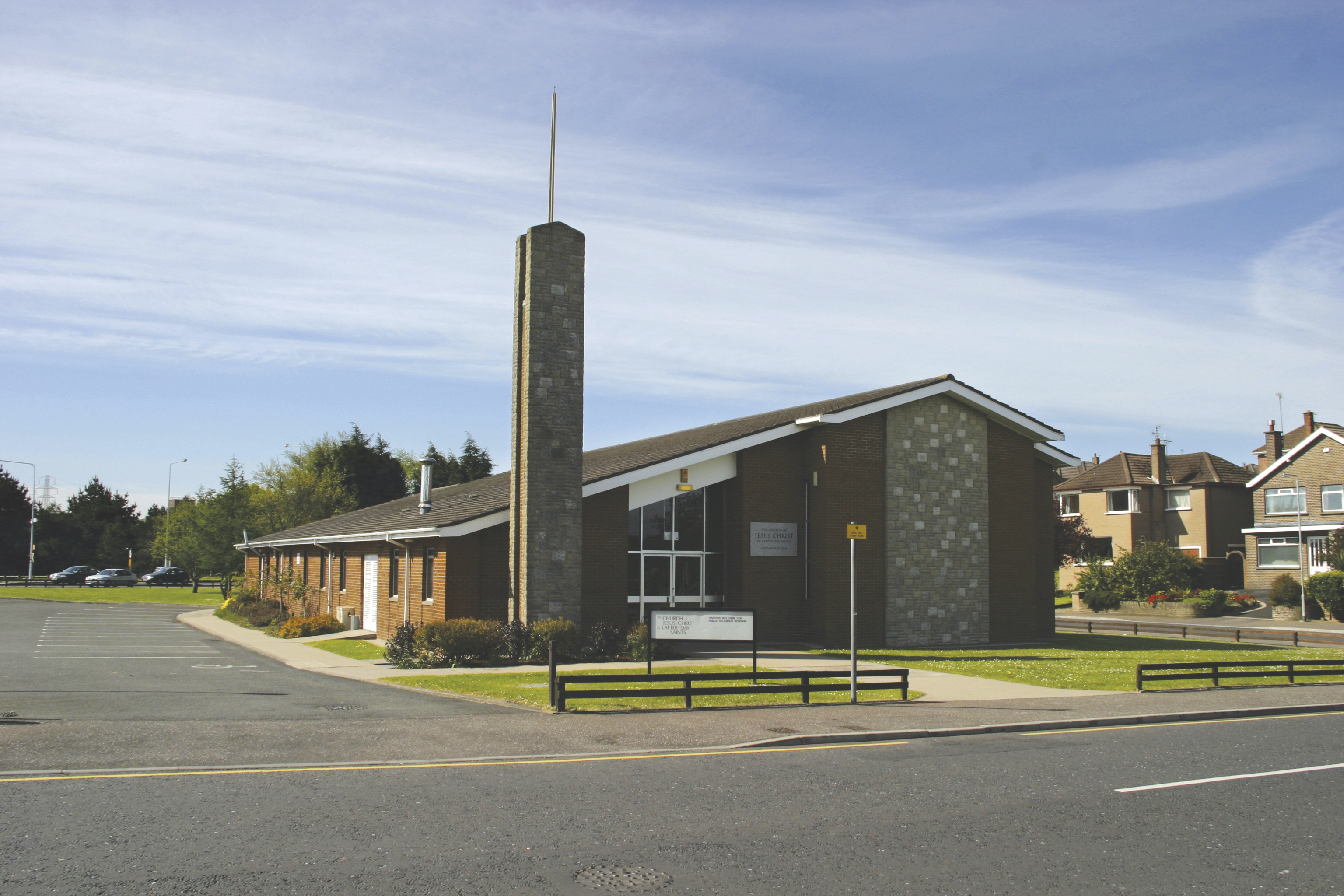 The outside of a chapel in Ireland next to a parking lot.