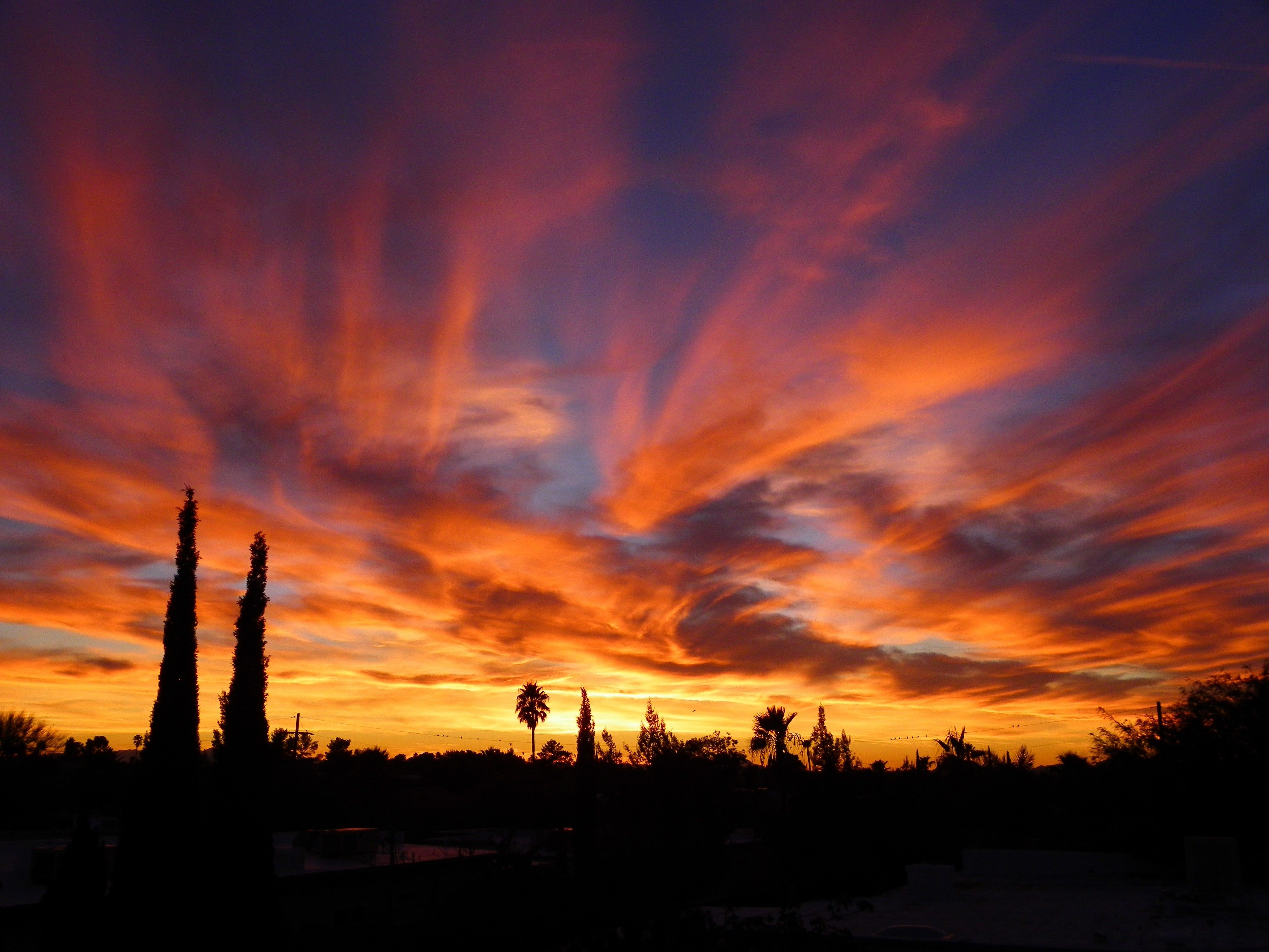 A sunset in Arizona turns clouds orange, yellow, and purple against a darkening blue sky.