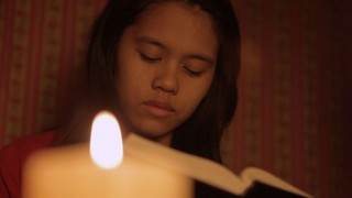 A girl reads the scriptures by candlelight