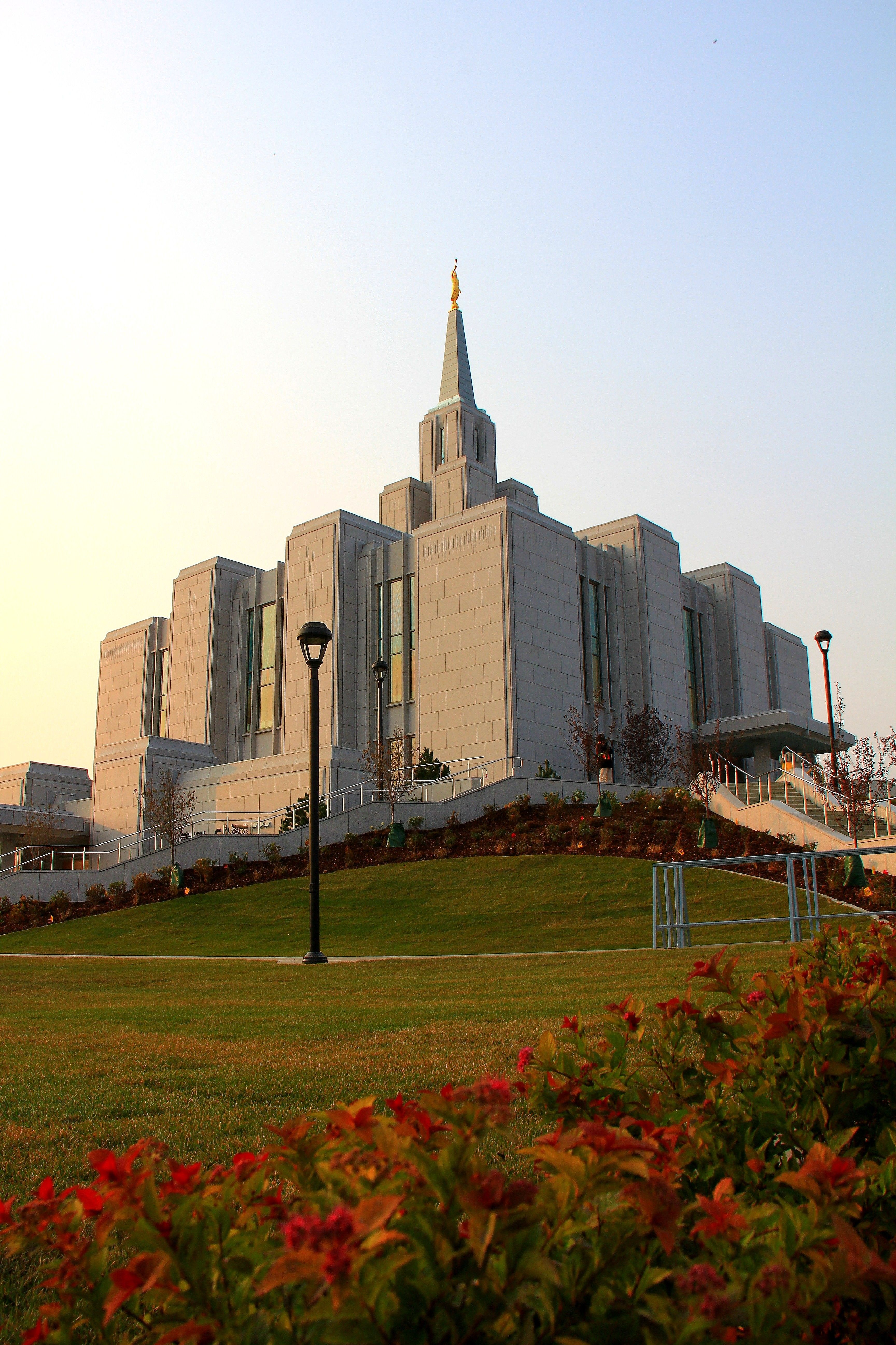 A portrait view of the Calgary Alberta Temple from the temple grounds during the evening.