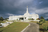 The entire Suva Fiji Temple, with stairs leading up to the entrance, a partial view of the grounds, and a path that goes through the grounds.