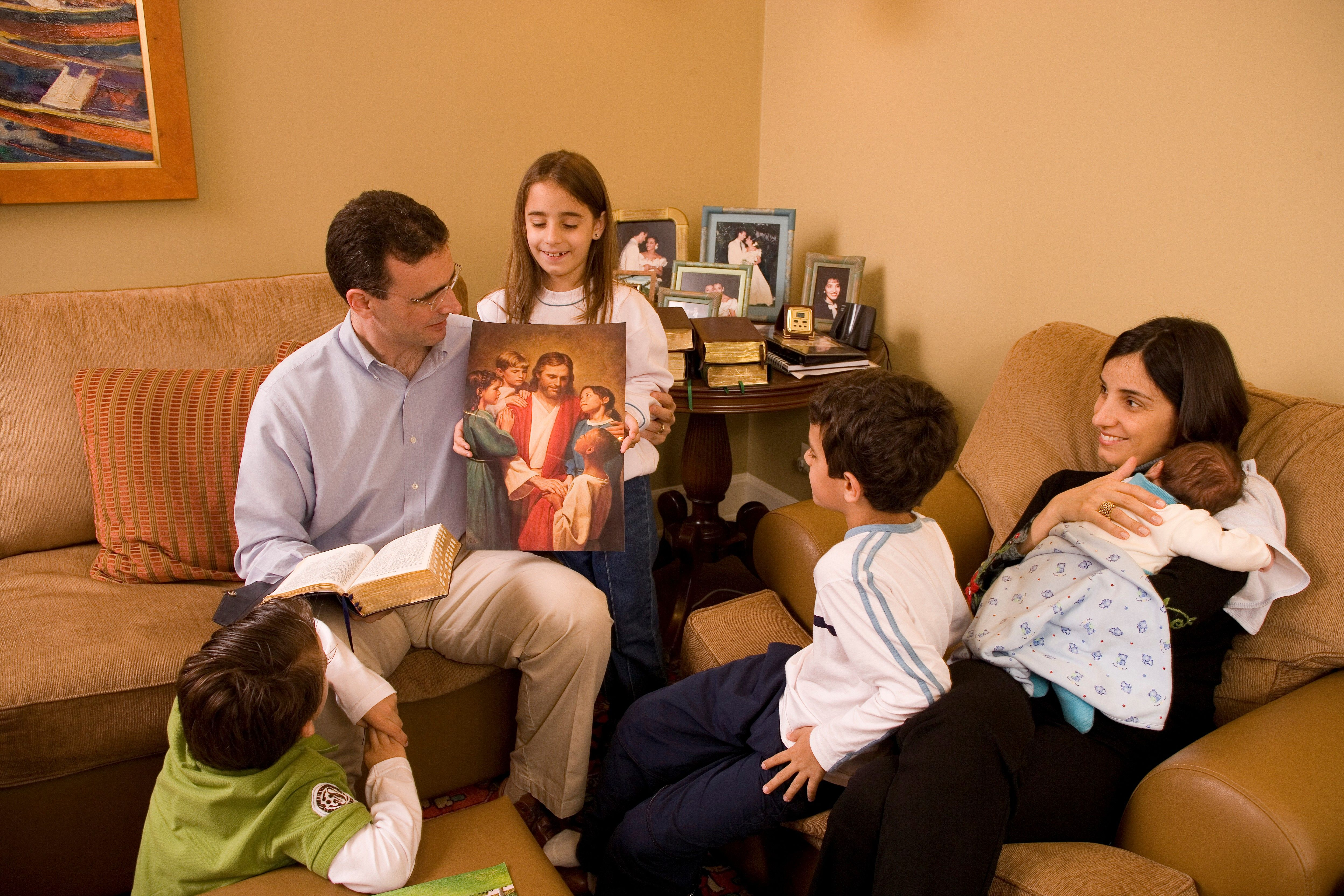 A family of six looking at an image of Christ with children during family home evening.
