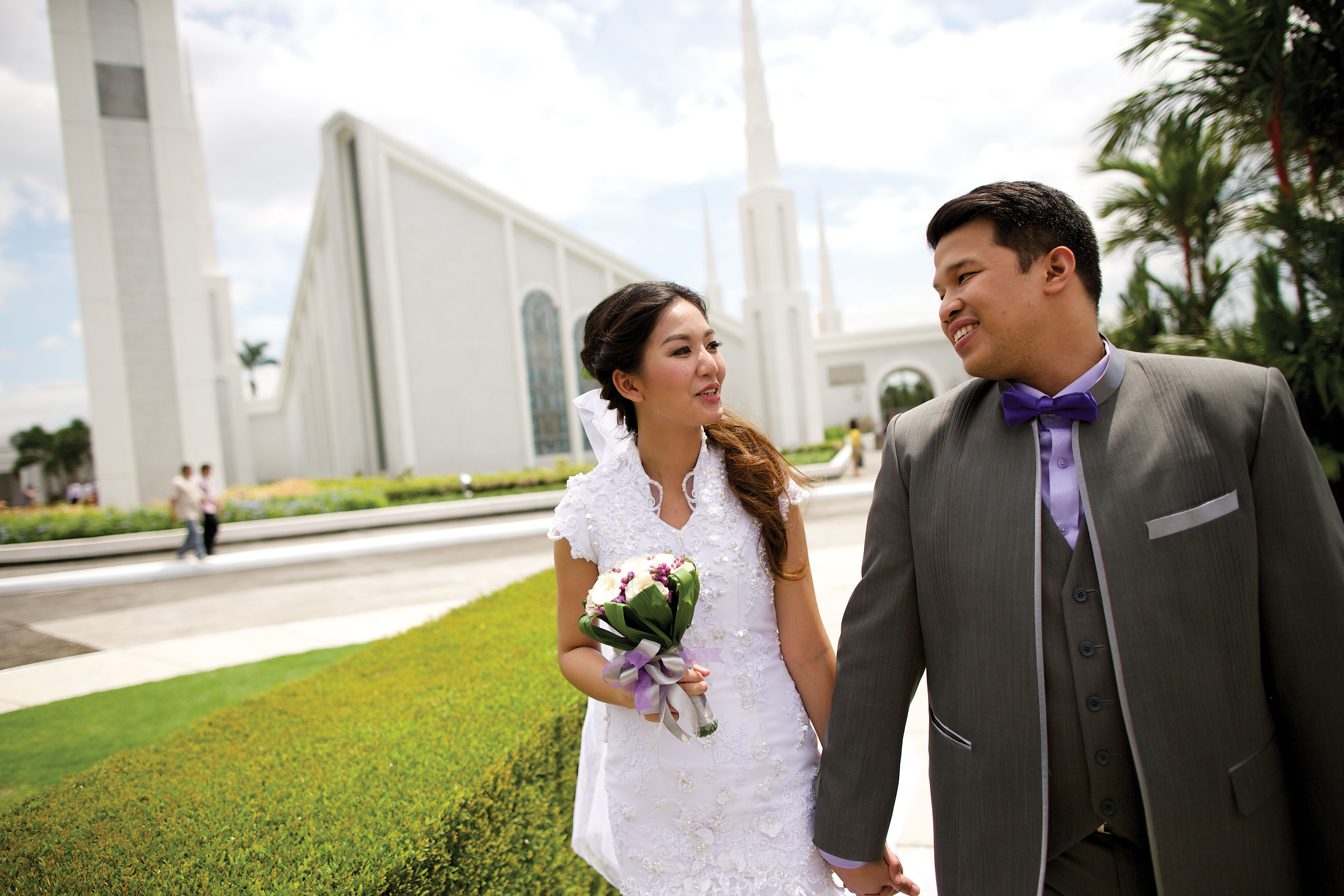 A bride and groom walking outside the Manila Philippines Temple.
