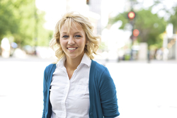 A young woman in a white buttoned shirt and blue sweater, standing outside in a downtown area and smiling.