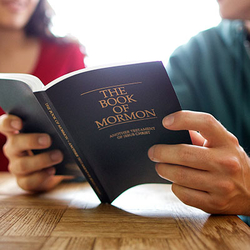 The Book of Mormon being read by a couple at a kitchen table