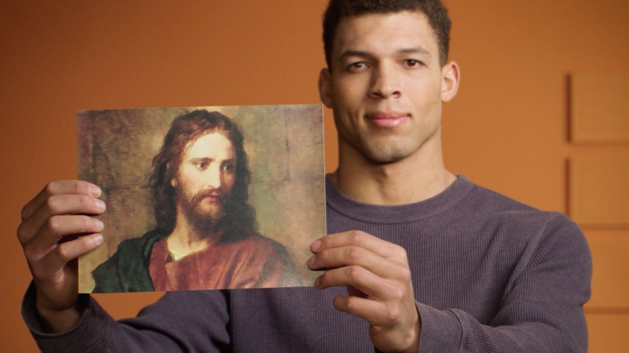 A man holding up a picture of Jesus Christ