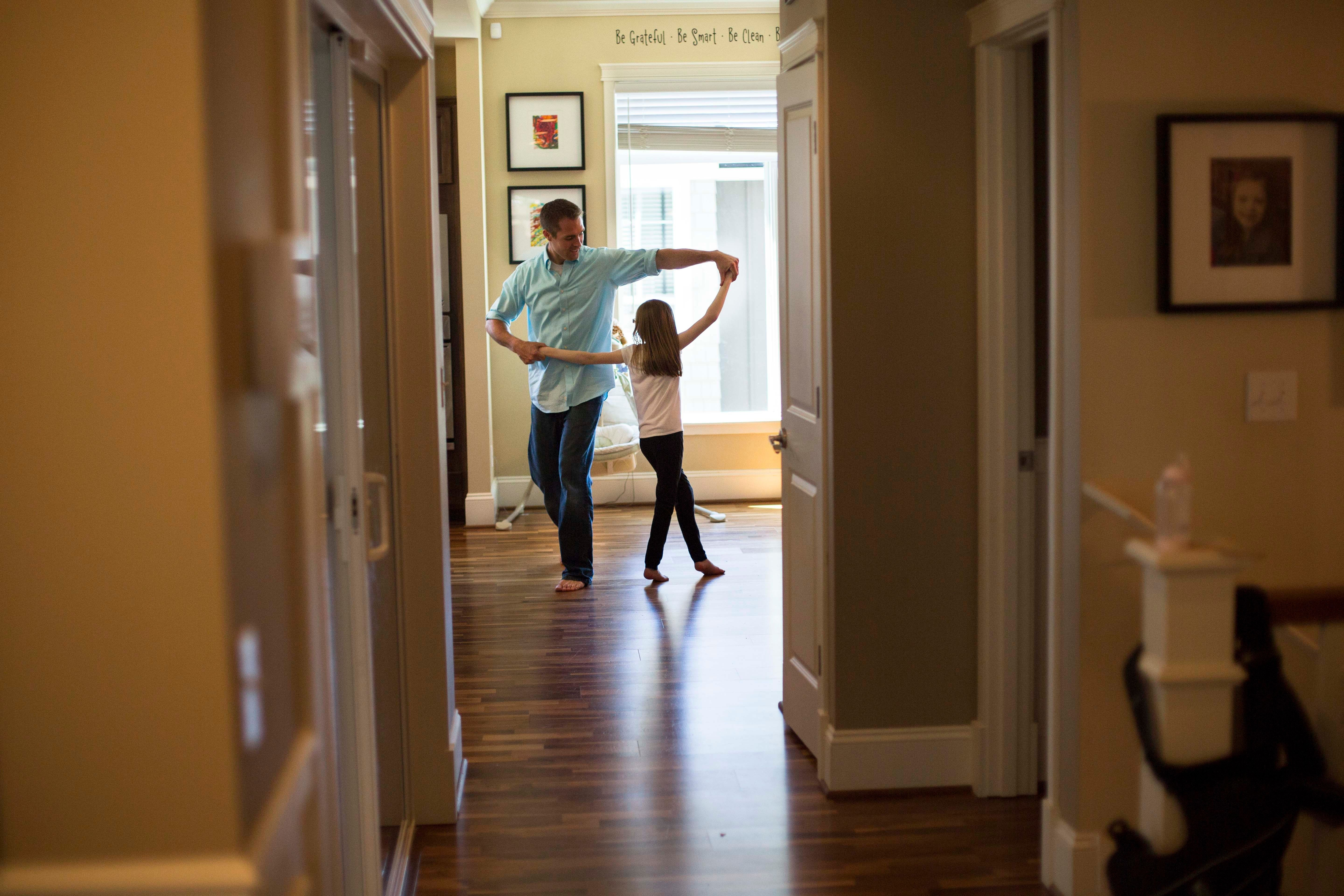 A father dances with his daughter in their home.
