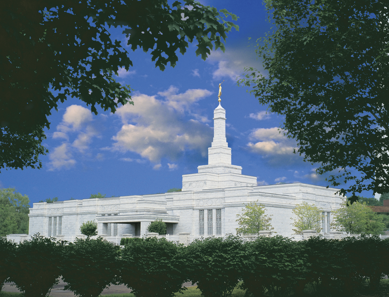 Trees and bushes around the Detroit Michigan Temple during the day, with a few clouds overhead.