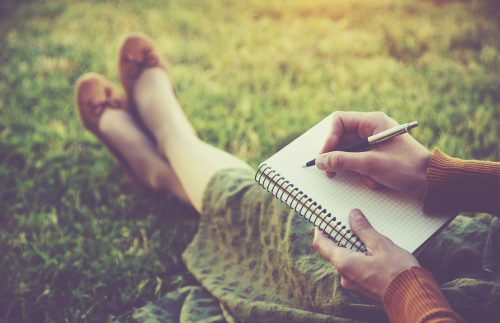 Girl Writing in Notebook on Grass