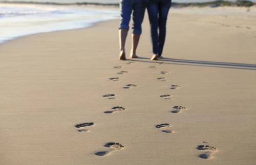 Couple Walking Across Beach Shoreline Leaving Footprints