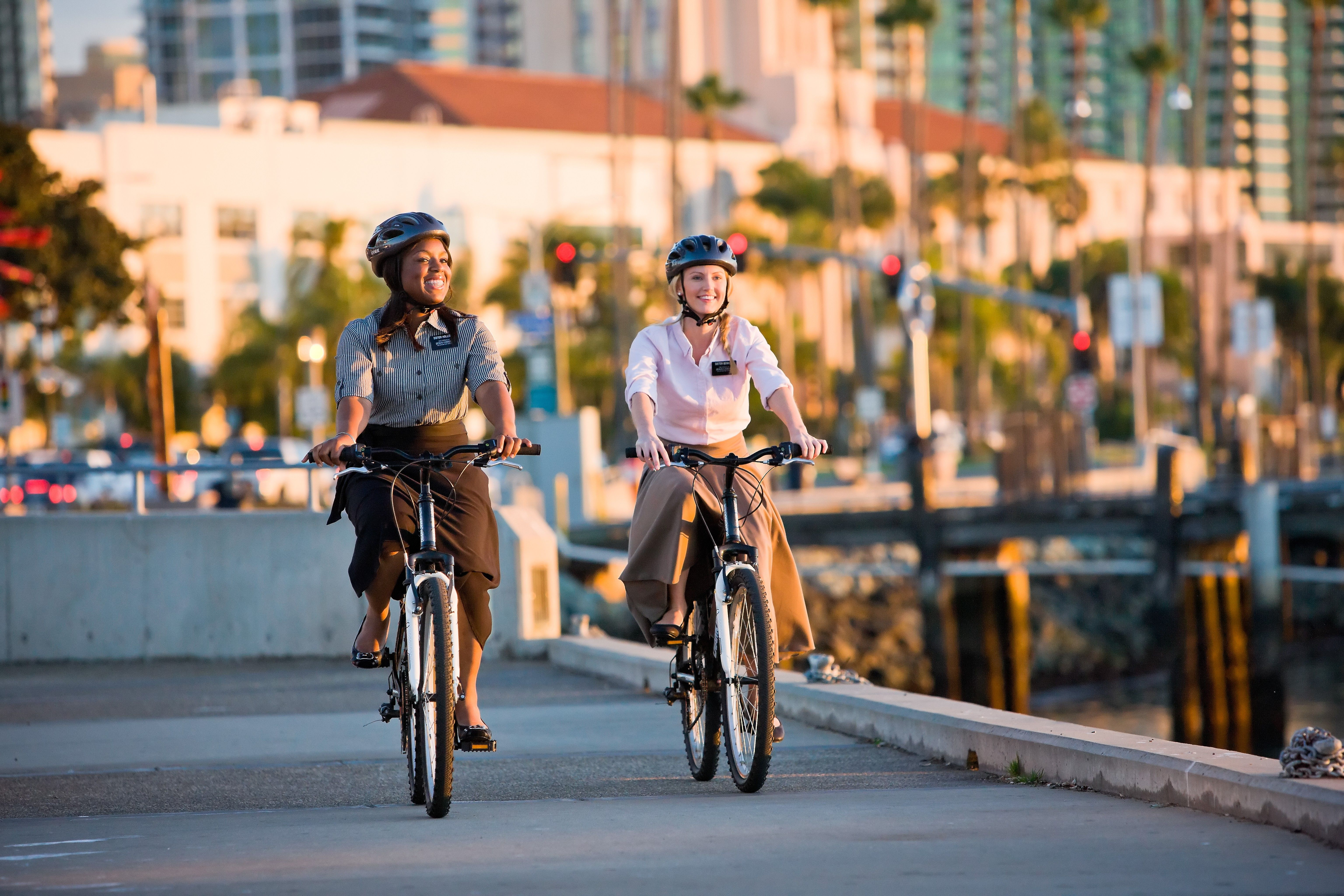 Two sister missionaries wearing helmets and riding bikes.