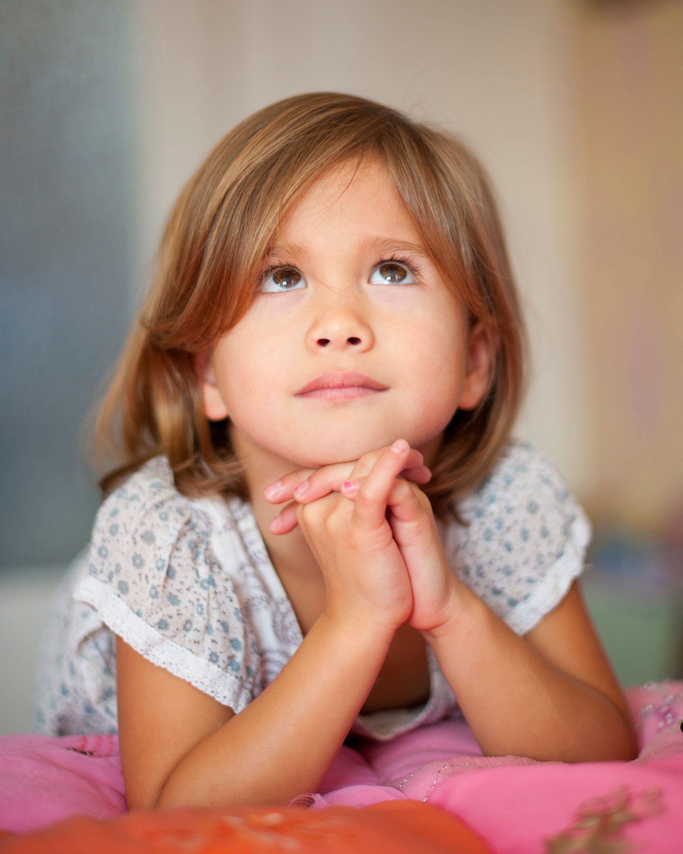 A girl prays kneeling down by her bed.