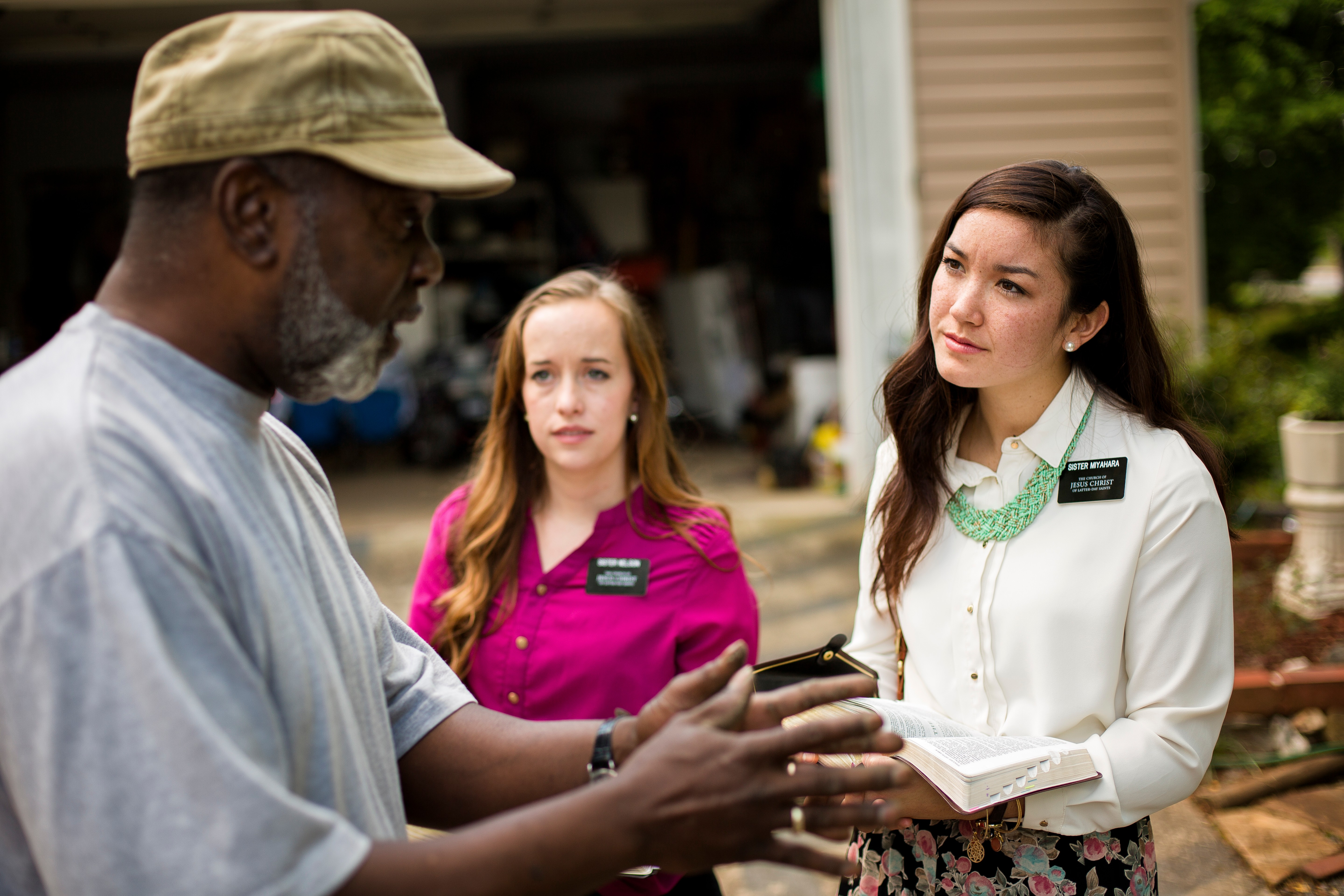 A man in Georgia standing and talking to two sister missionaries outside.
