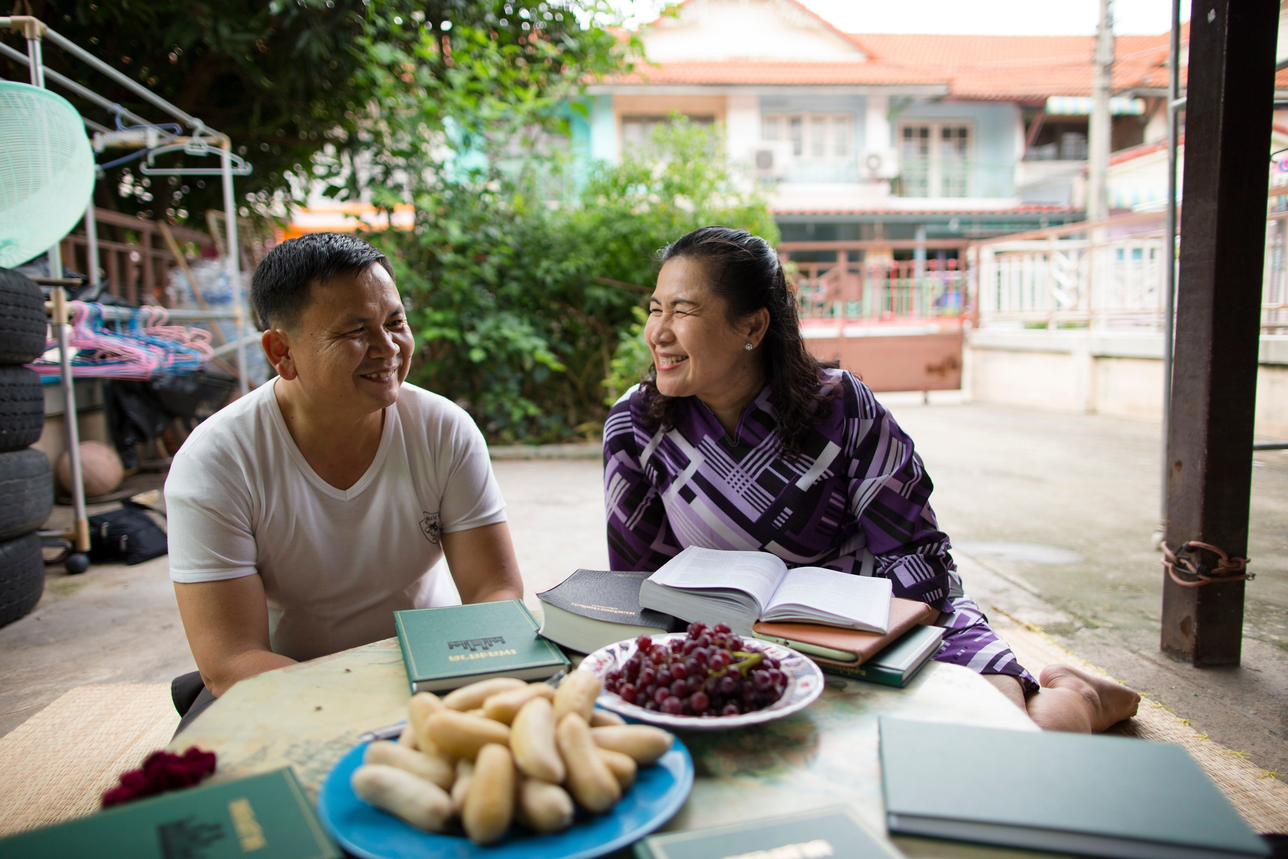 A couple from Thailand smiling and sitting at a table with gospel books.