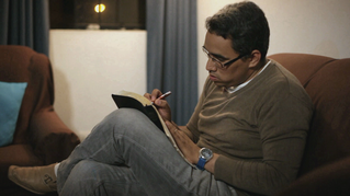 A photo of a man sitting on a chair writing in his scriptures.