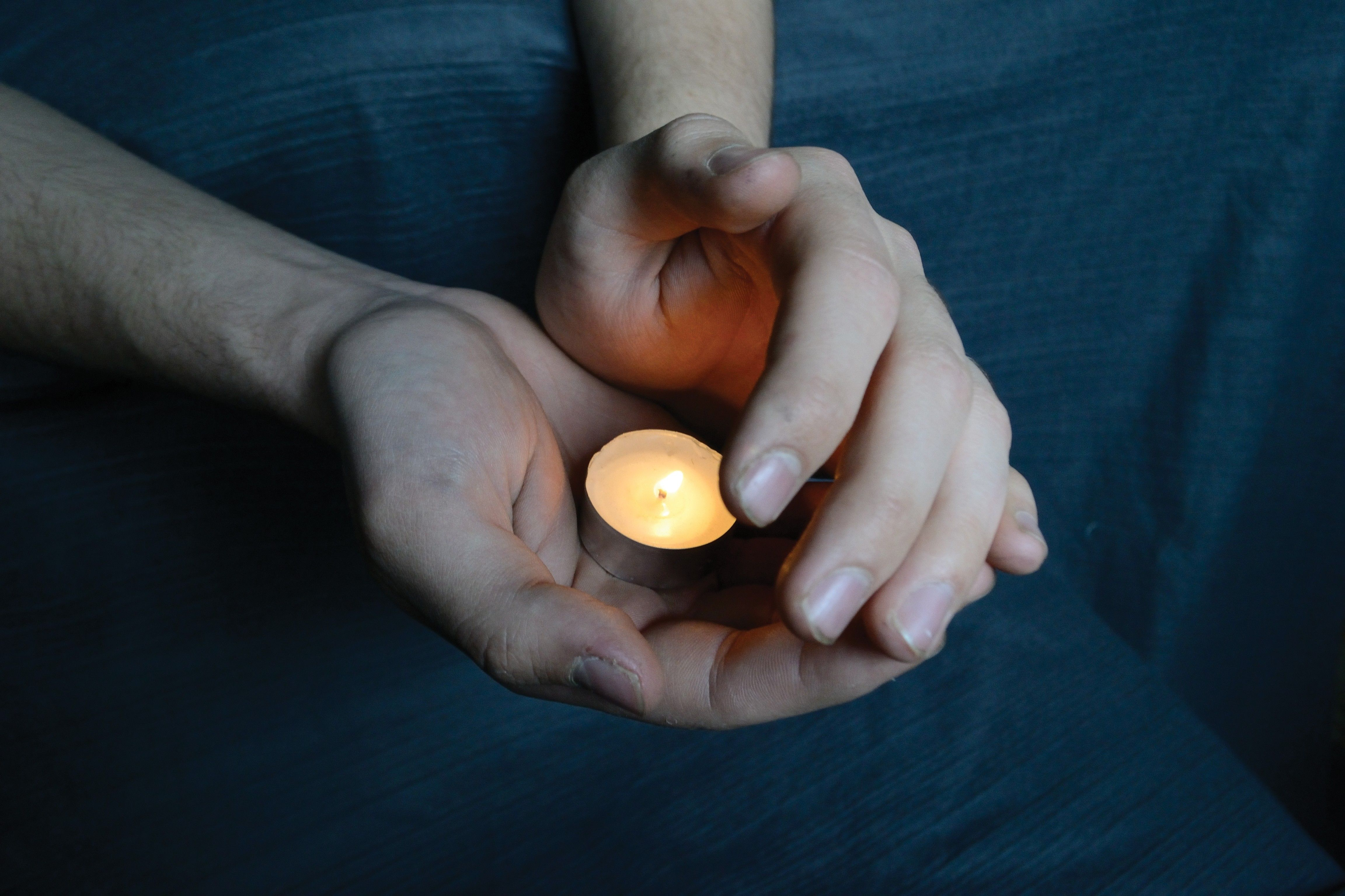 Hands holding a candle in the dark, sheltering the flame from the wind.