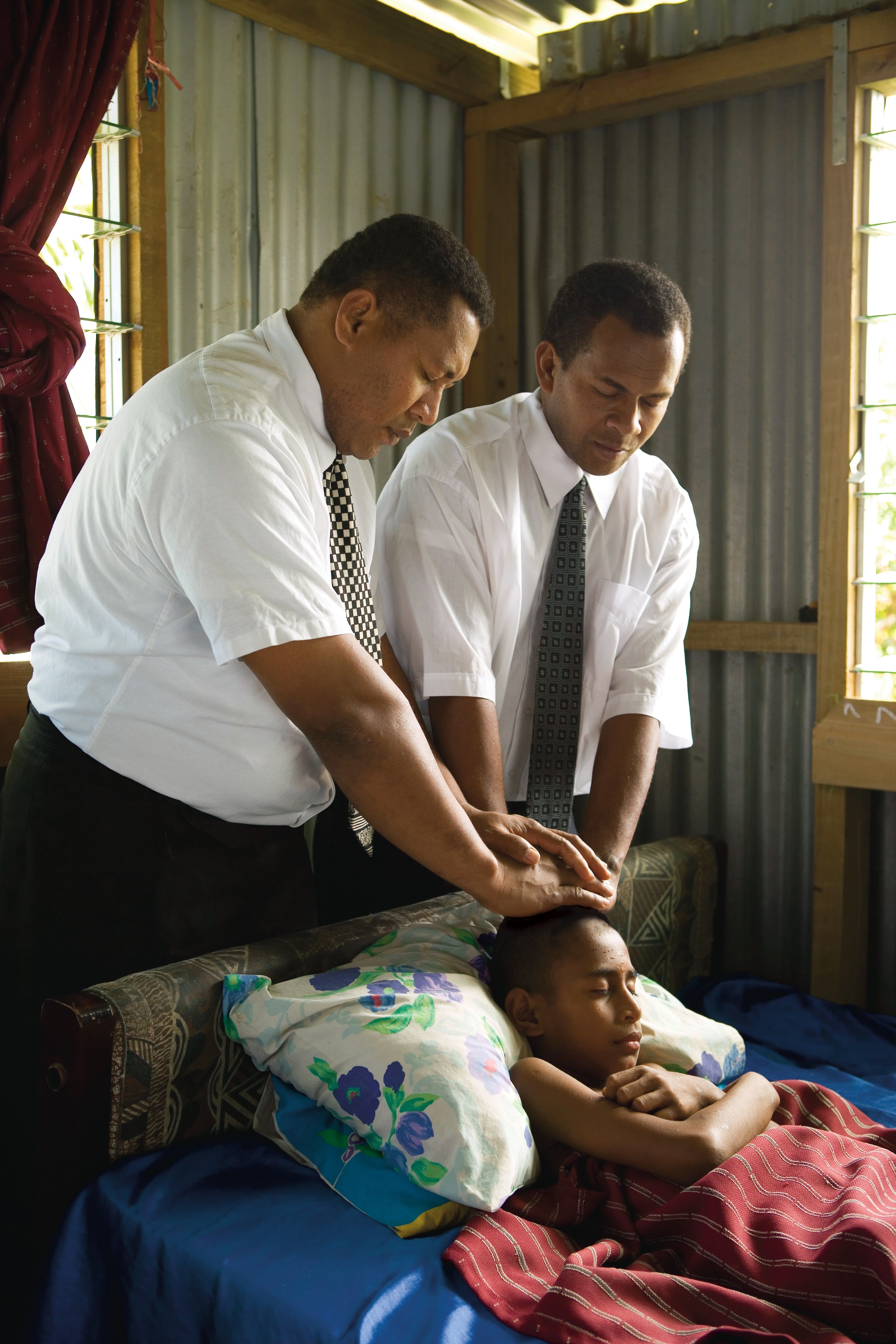 Two men give a priesthood blessing to a young boy who is sick.