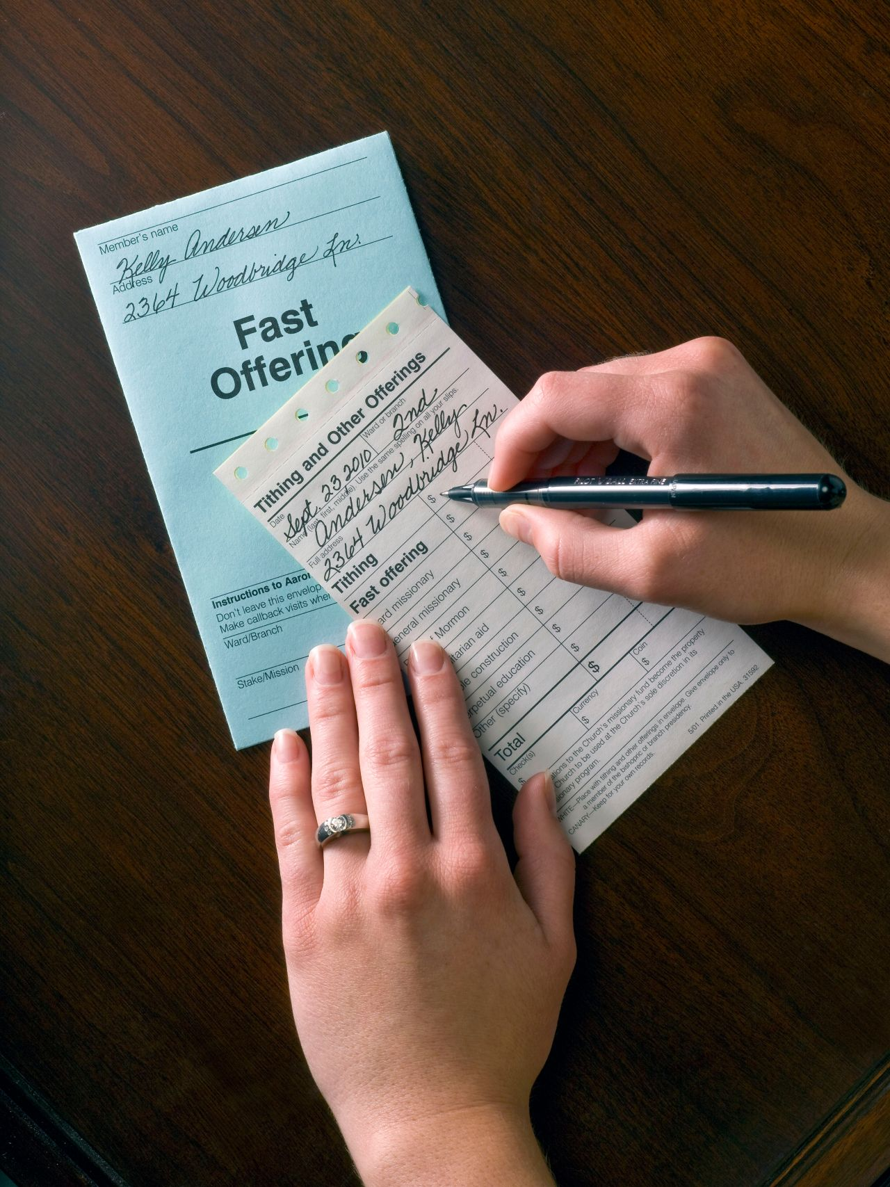 A woman fills out her tithing slip at her kitchen table