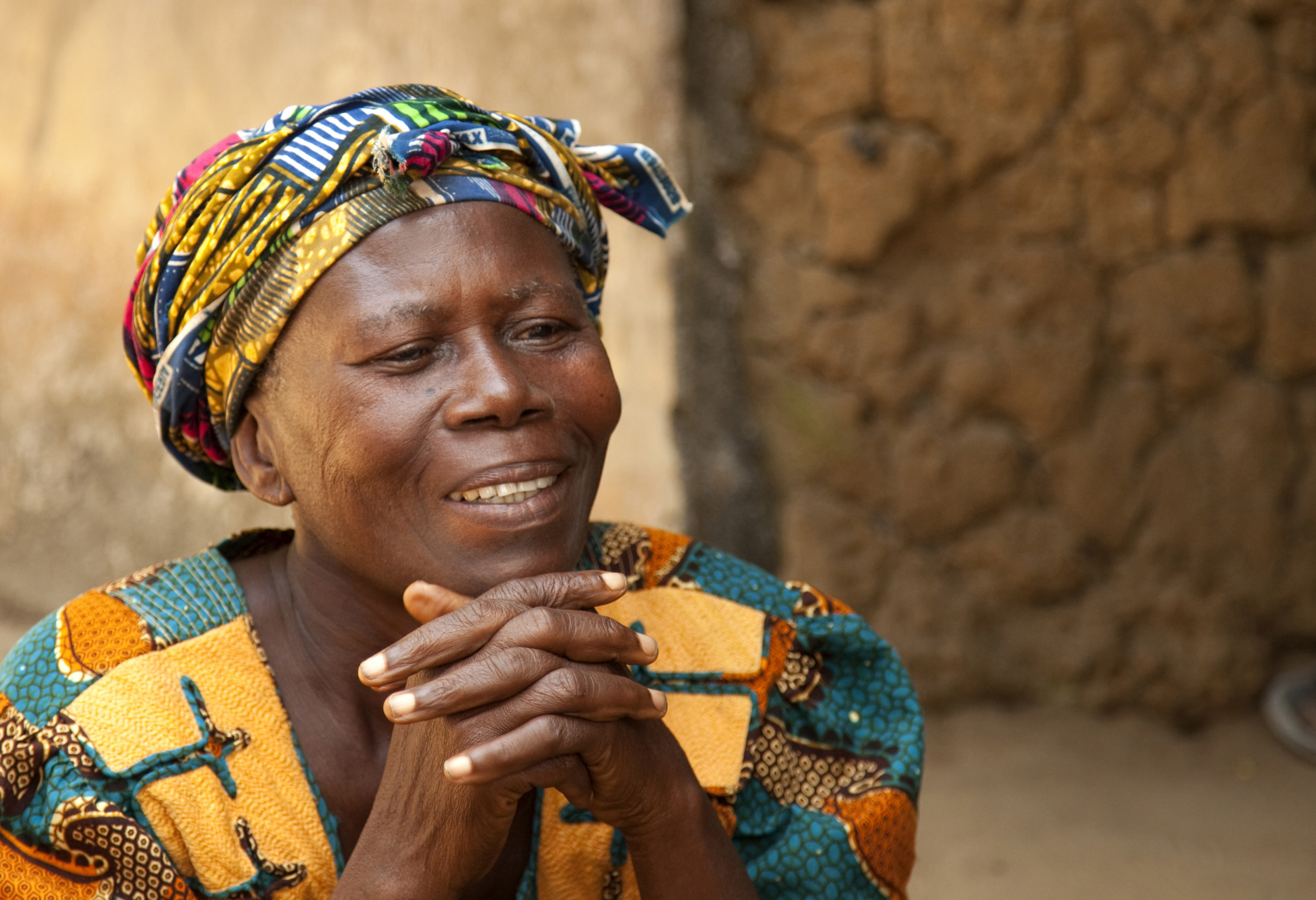 An African woman in a colorful head wrap and shirt clasping her hands together.