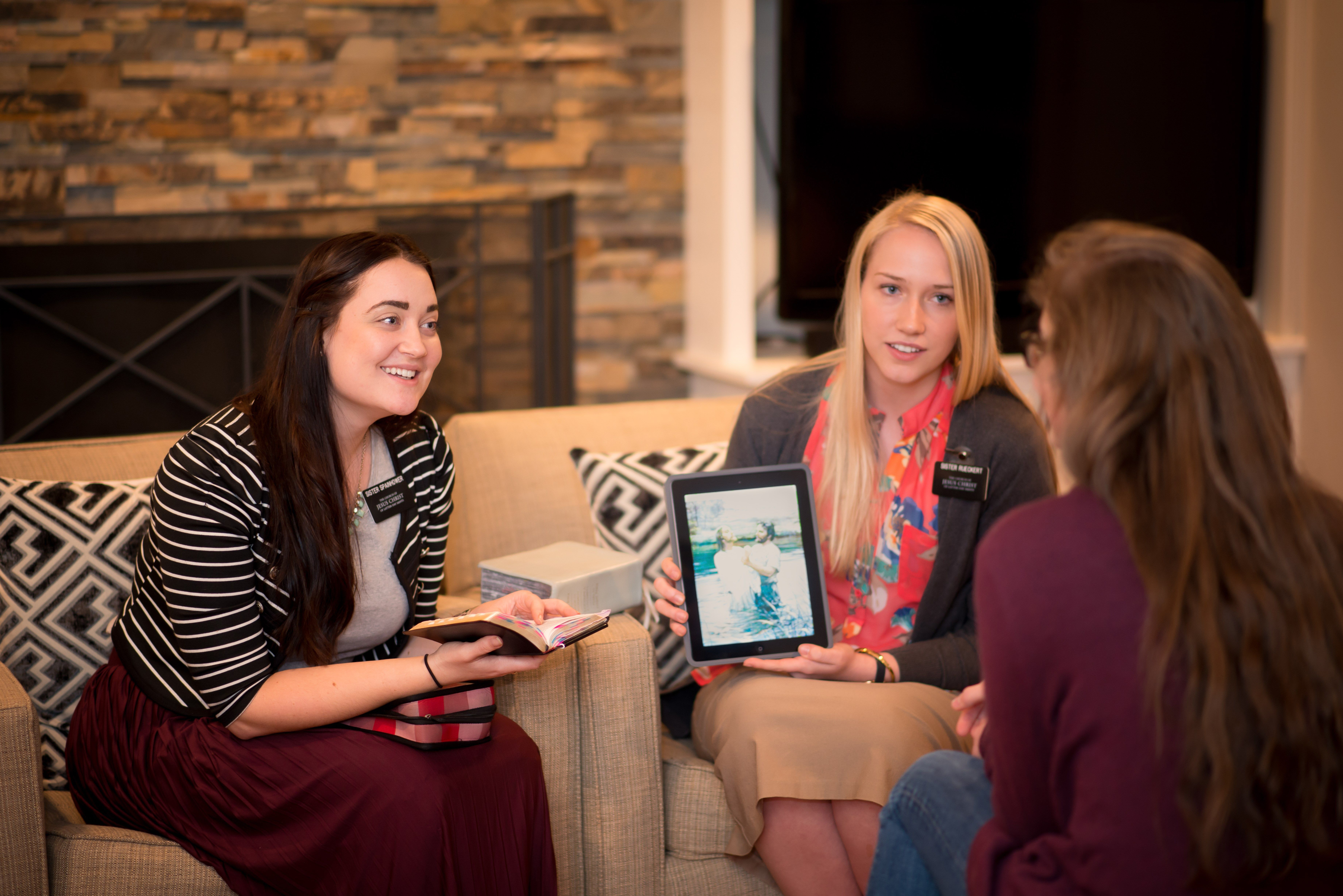 Two sister missionaries teaching a woman with their scriptures and an iPad.