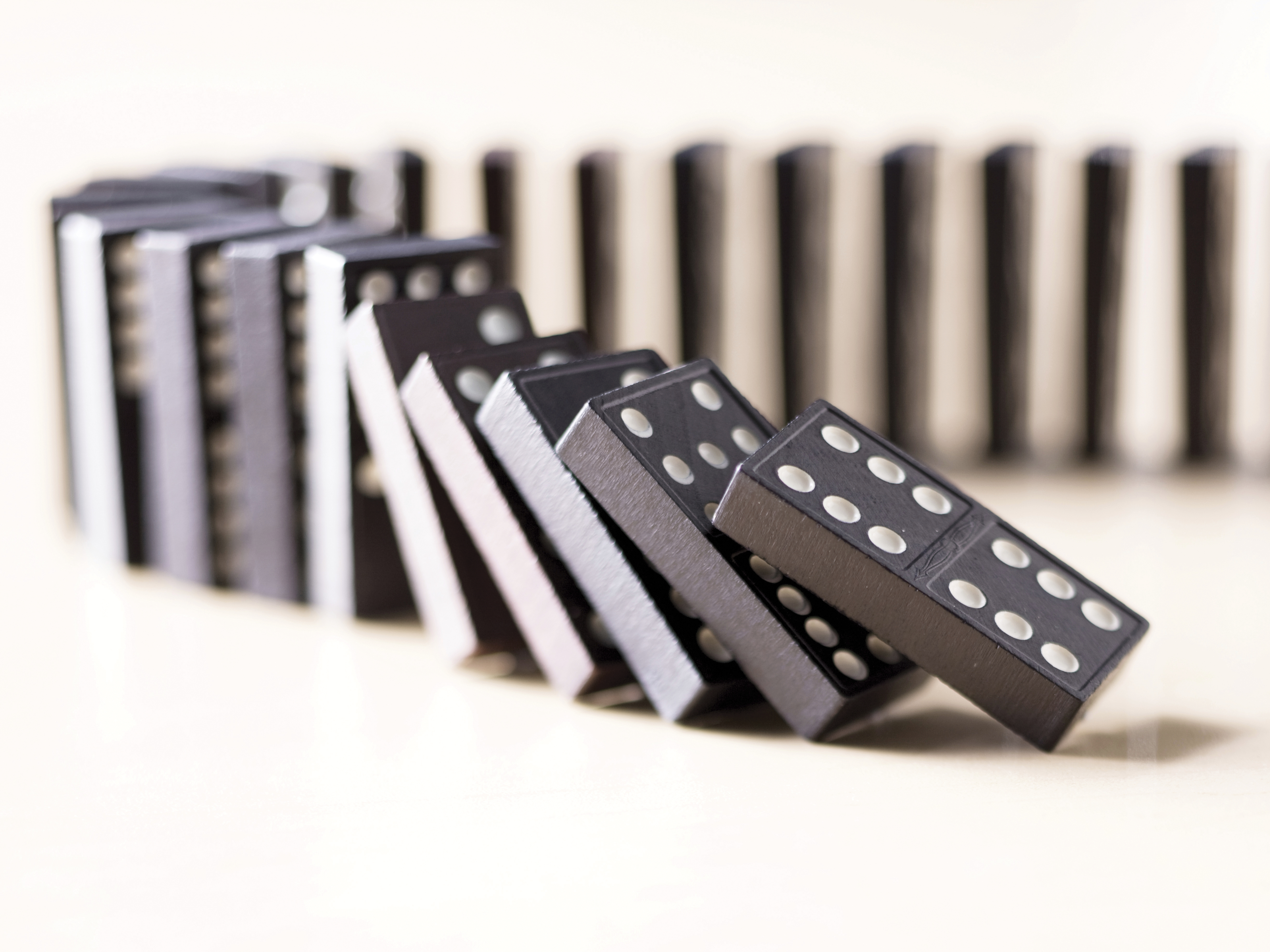 A row of dominoes tipping over in succession.