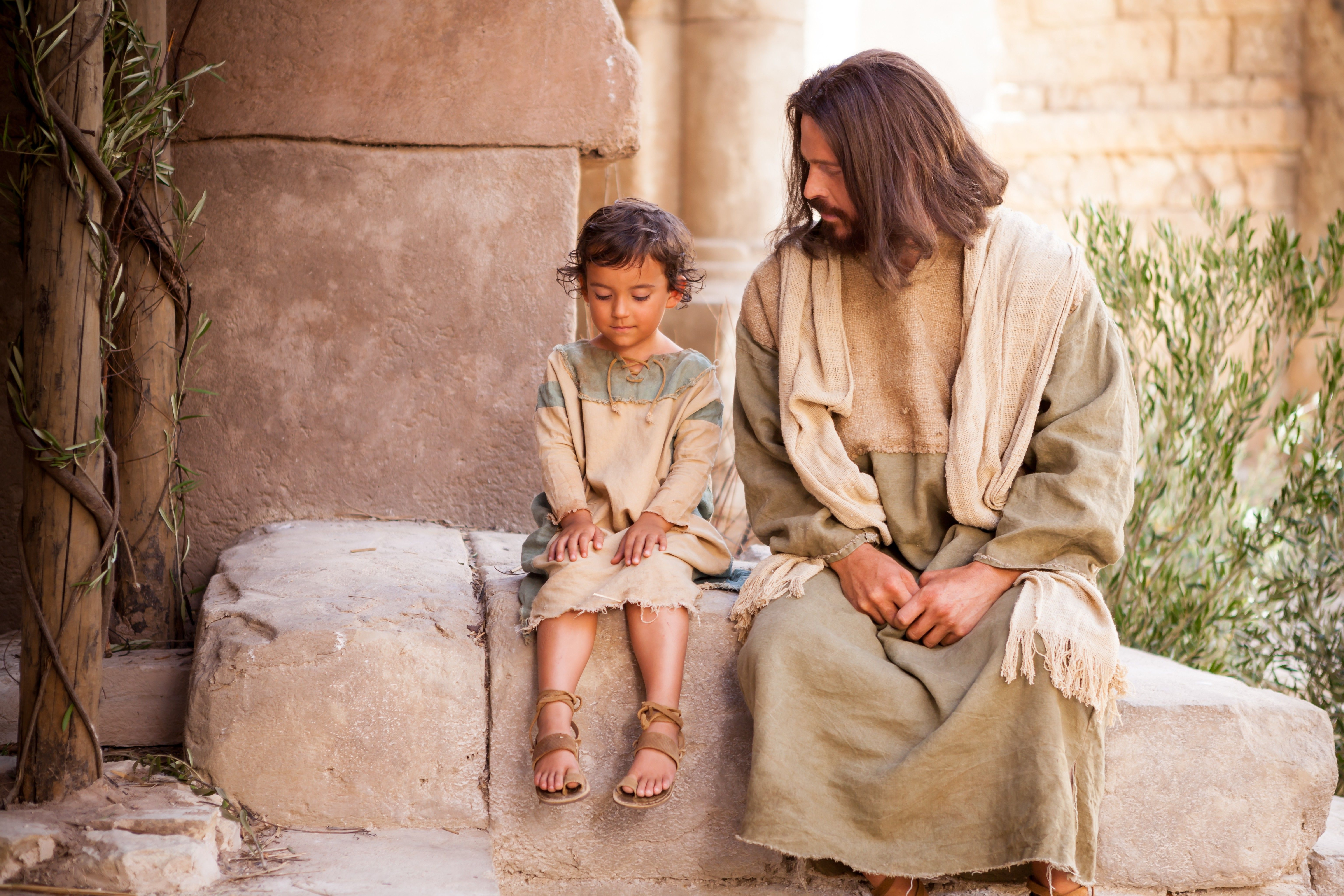 "Christ sits with a young child while teaching that we must ""become as little children."""