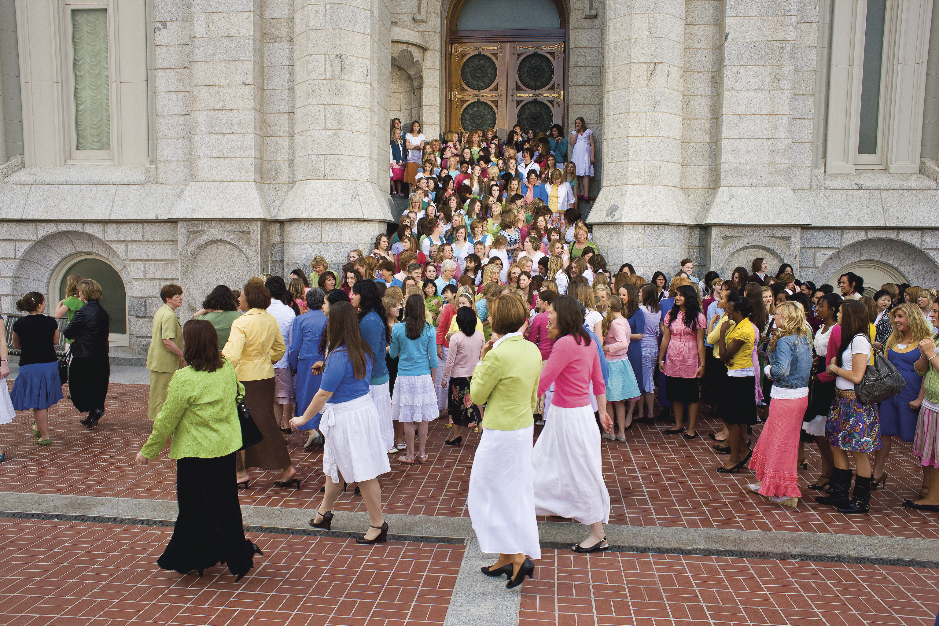 A large group of young women and their leaders standing on the Salt Lake Temple stairs.