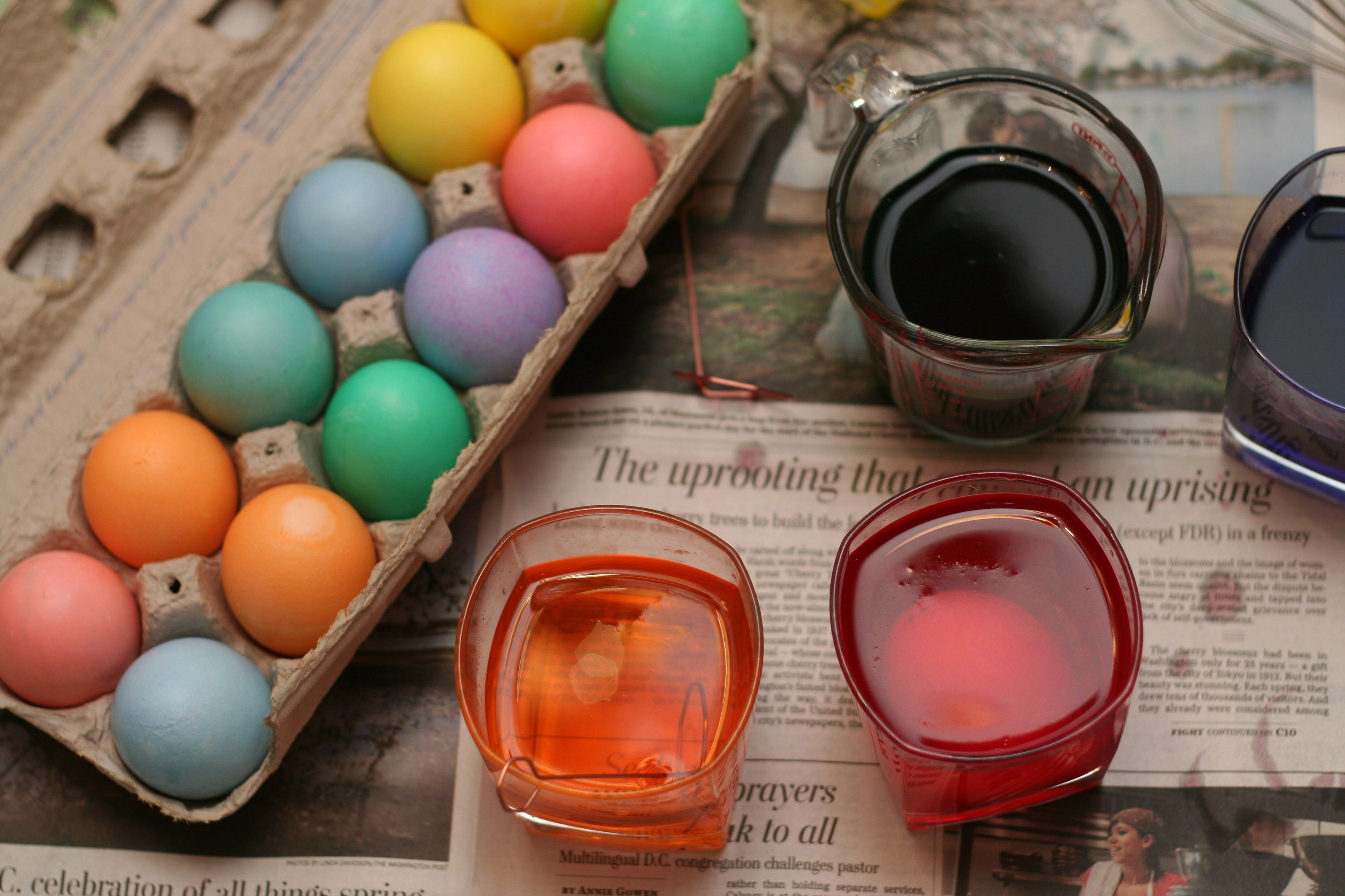 Several cups of Easter egg dye near a carton of newly colored eggs.