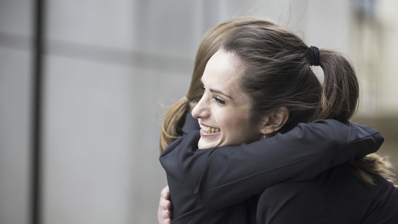 Two women hug and forgive each other