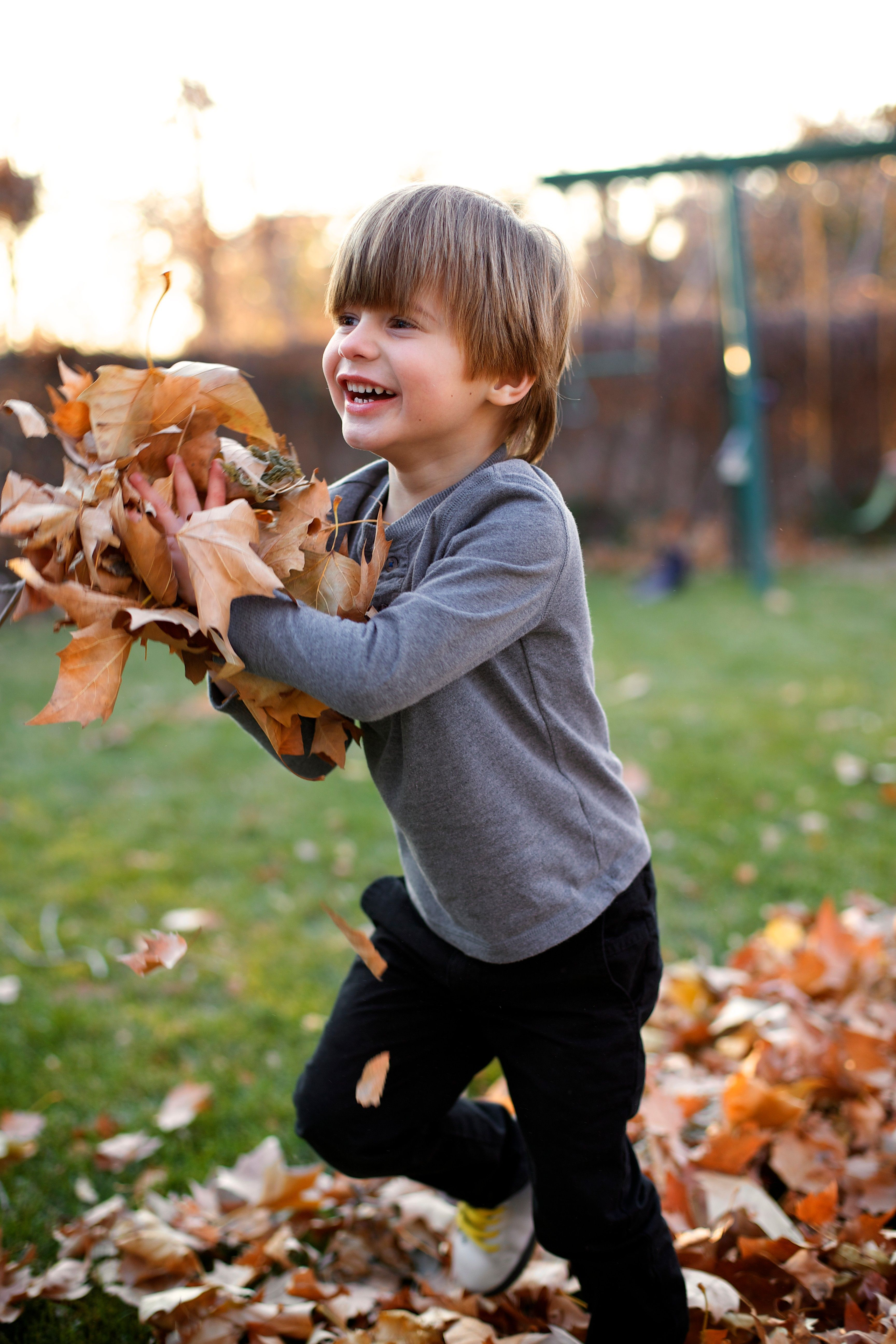 A young boy playing and running with a pile of leaves in his hands.