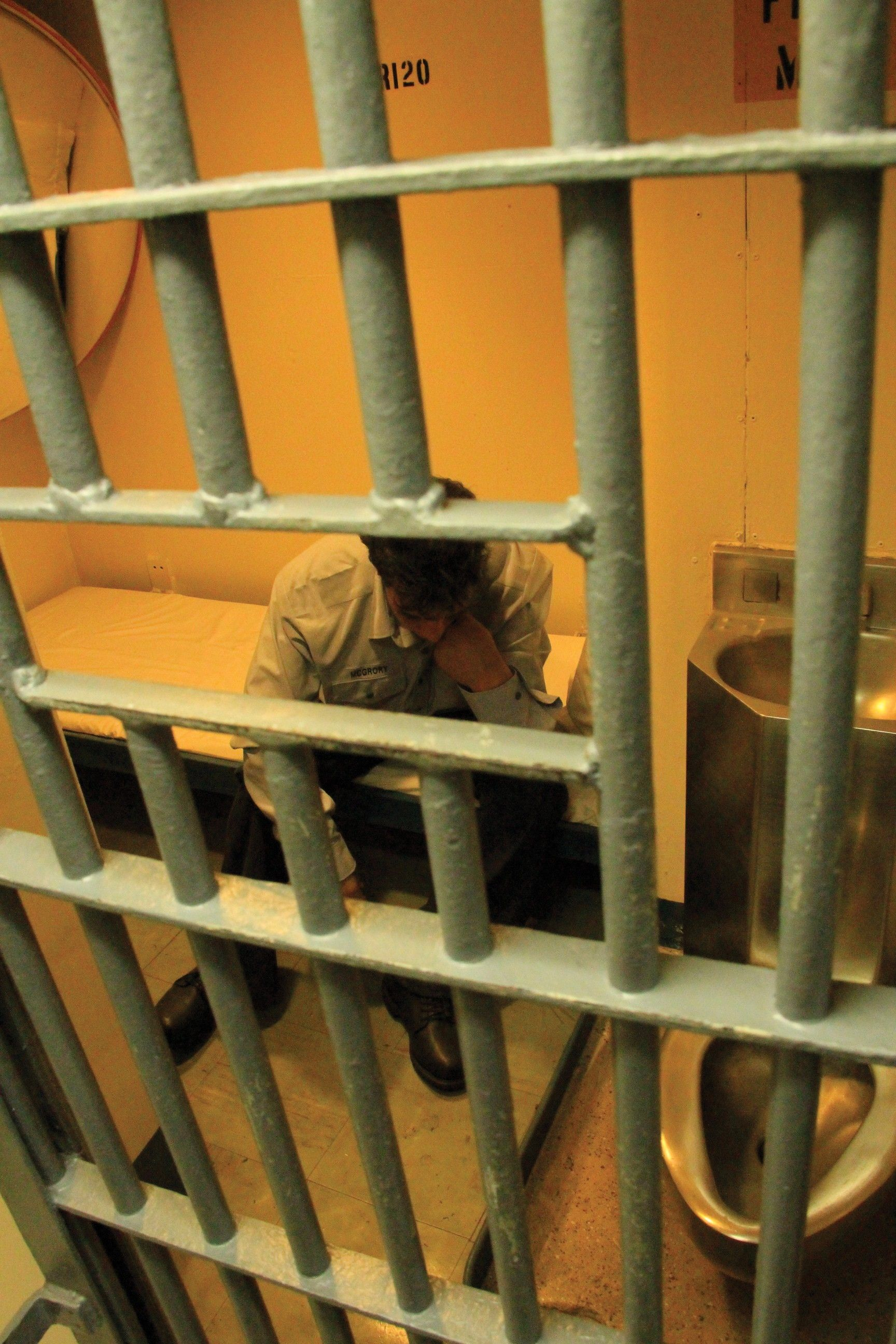 A man sitting in a prison cell looking discouraged.