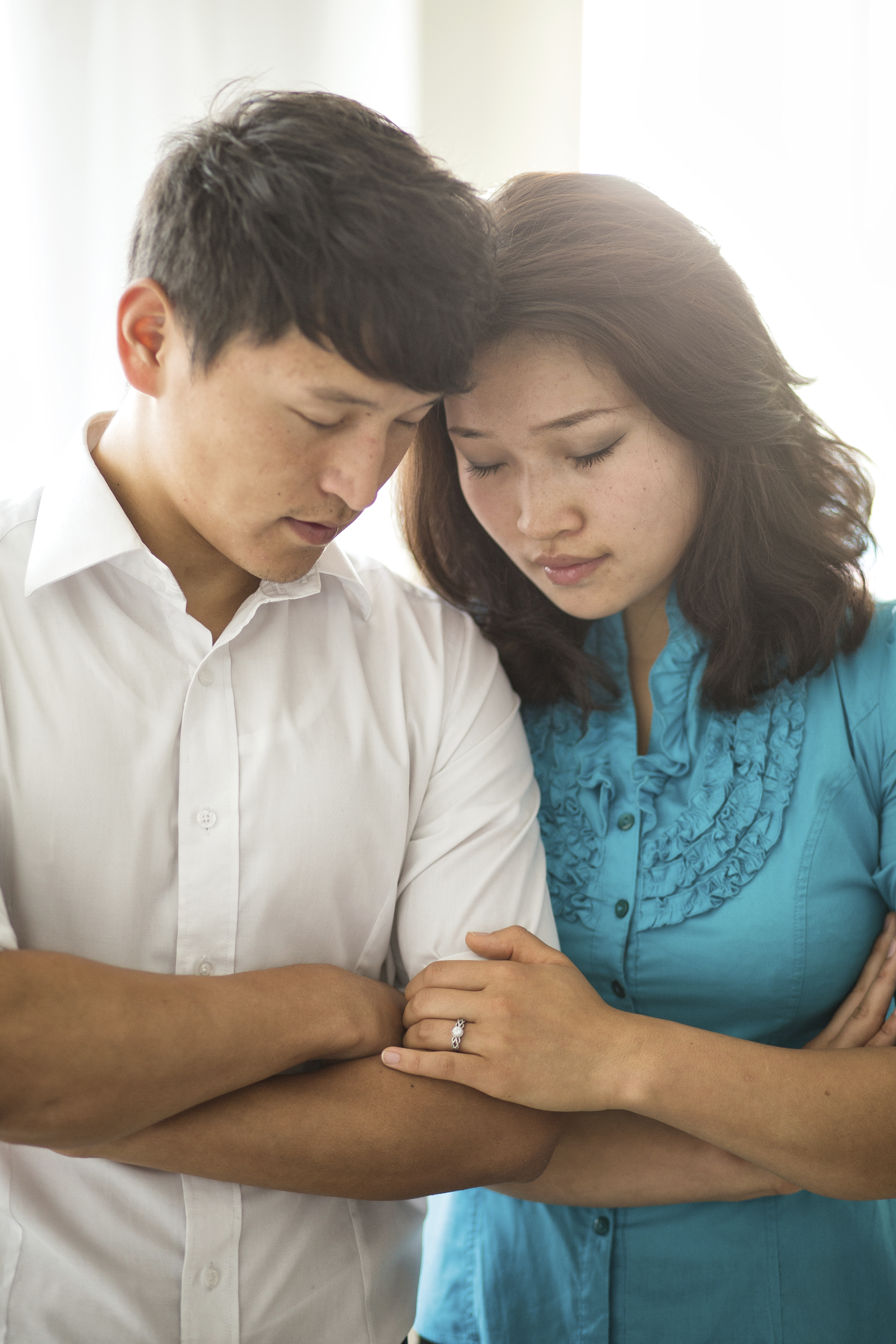 A young couple from Mongolia standing and praying together.