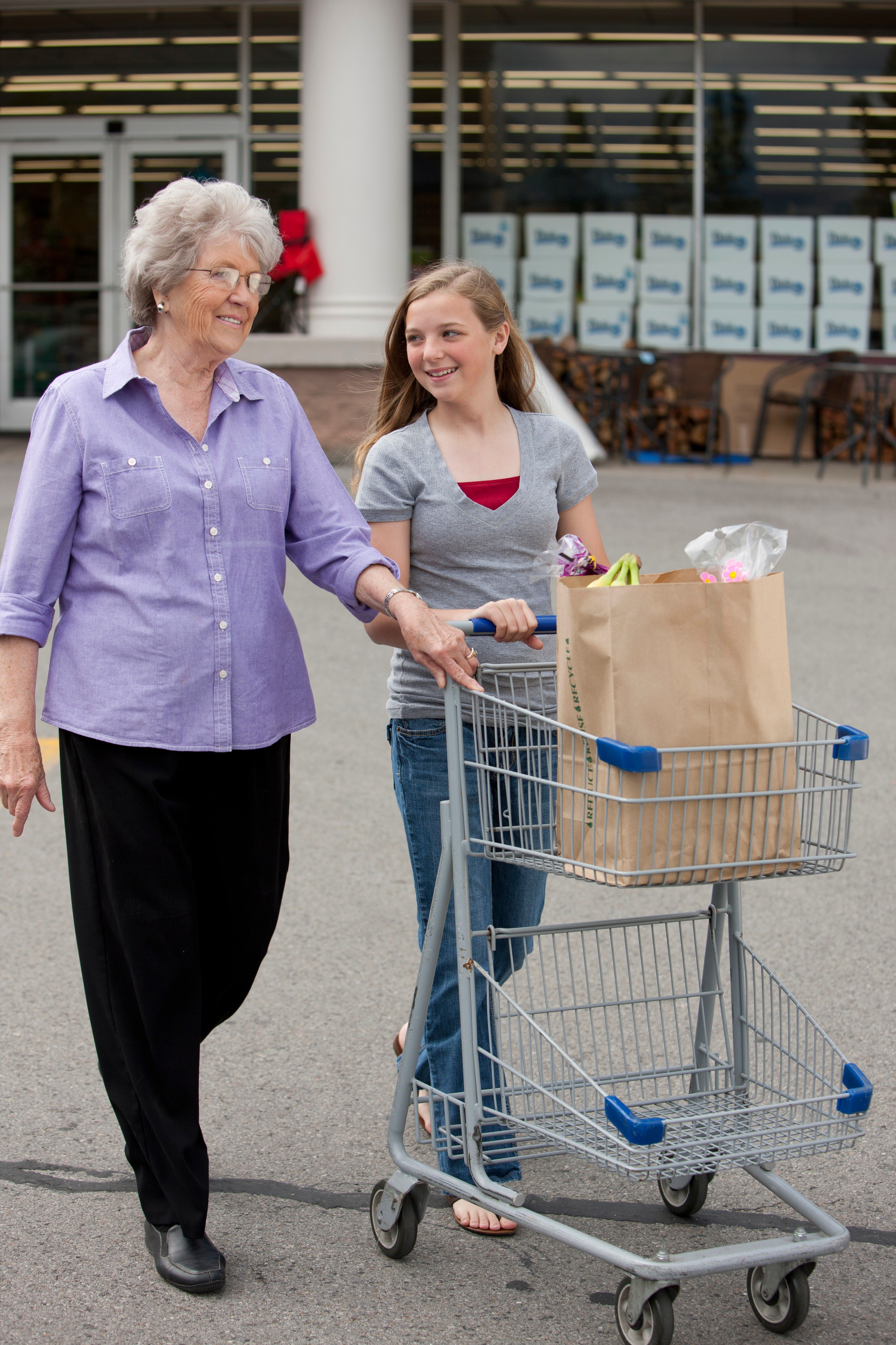 A young woman helps push a cart for an elderly woman with her groceries.