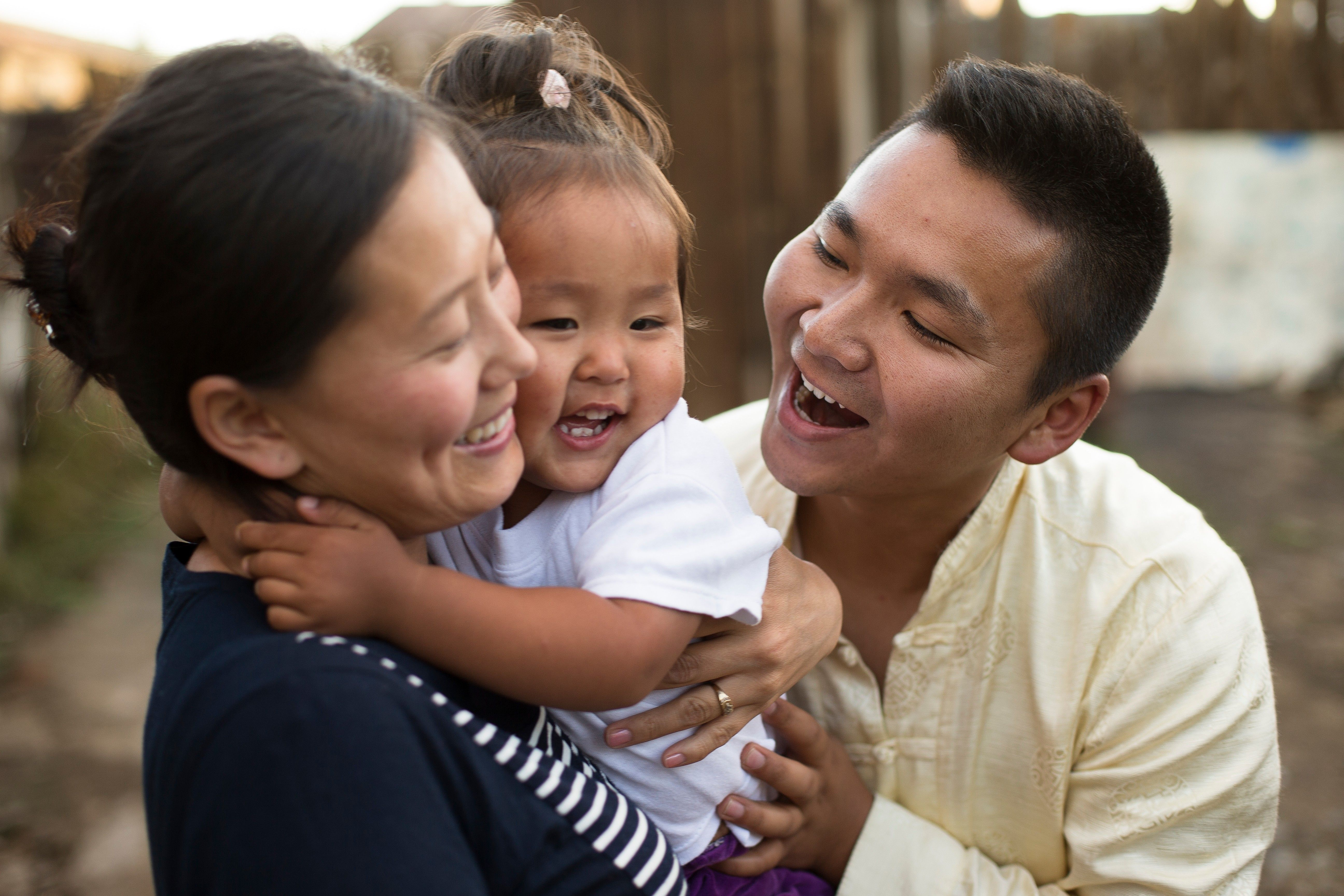 A young family in Mongolia laugh together in a happy moment.