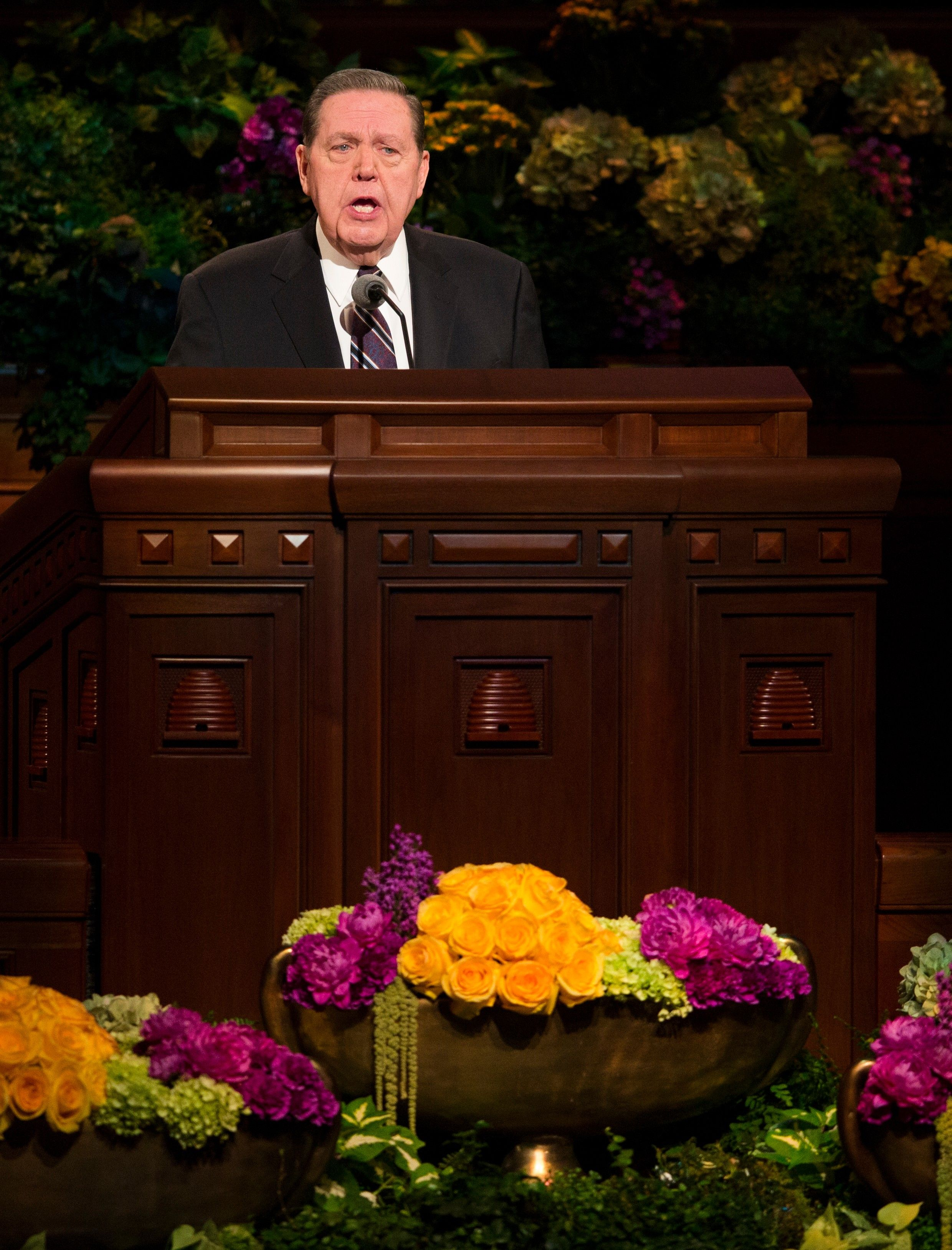 Jeffrey R. Holland standing and speaking behind the pulpit in general conference.