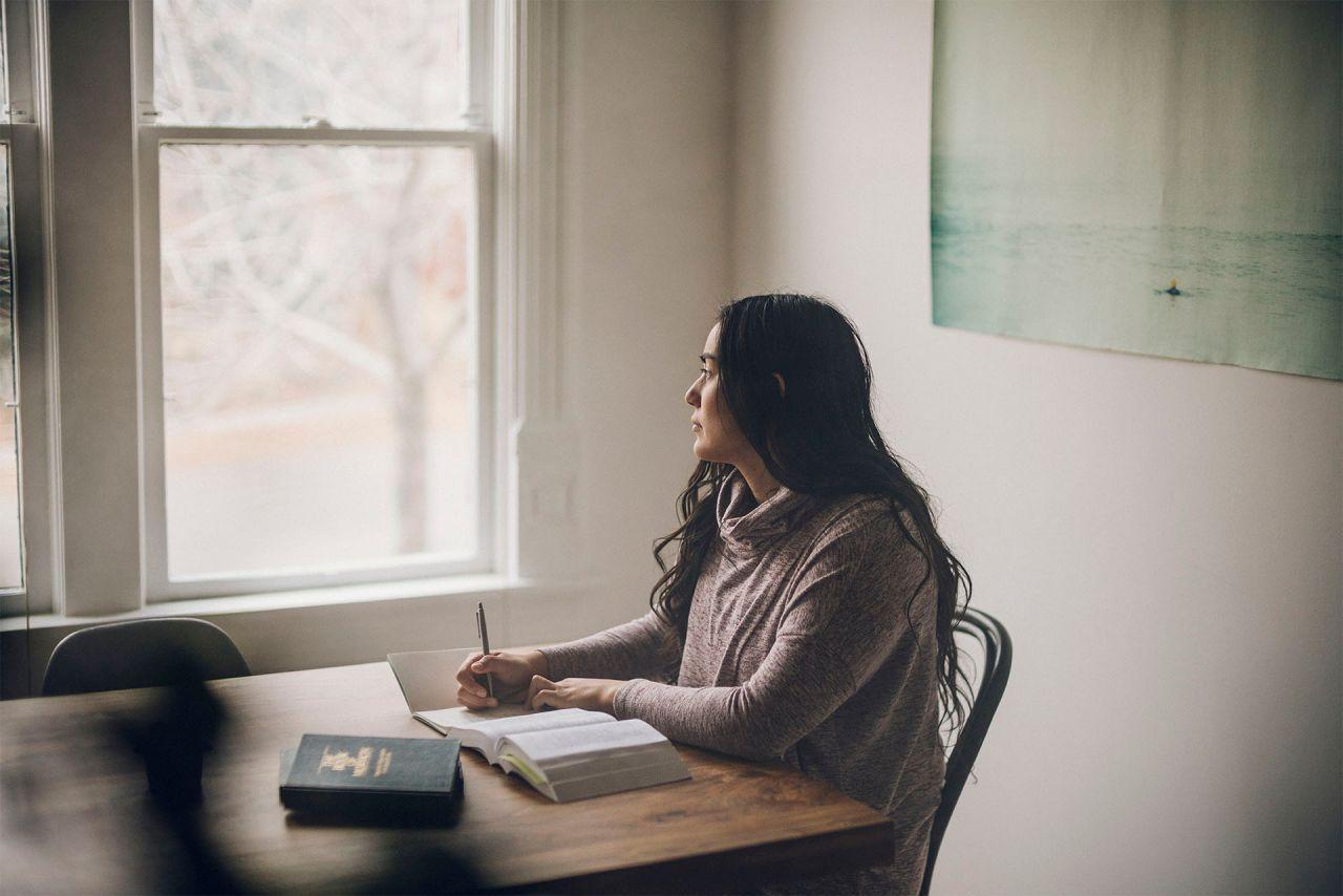Una mujer leyendo el Libro de Mormón y meditando sobre Dios