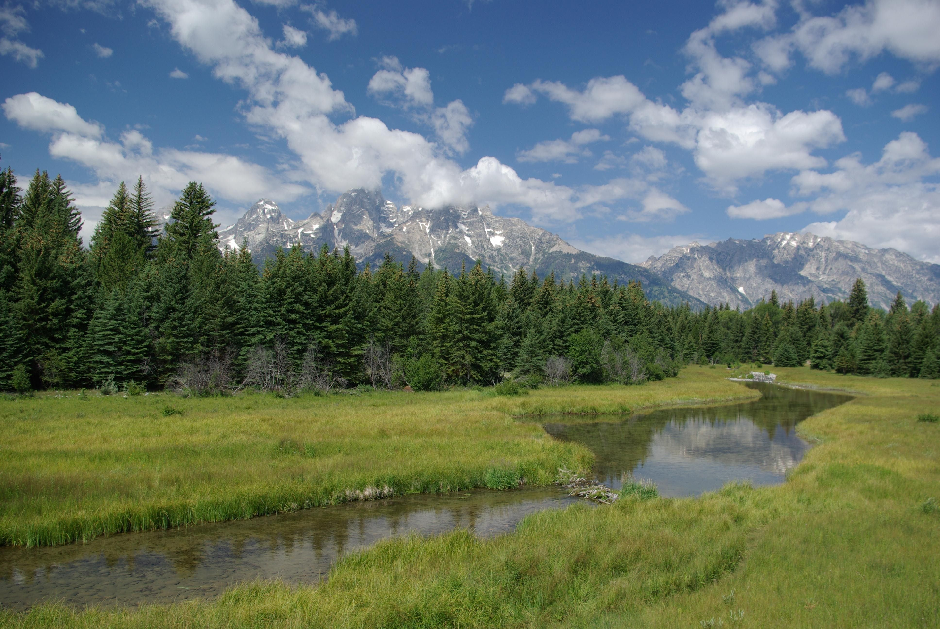A river runs through Grand Teton National Park with the mountain range in the background.