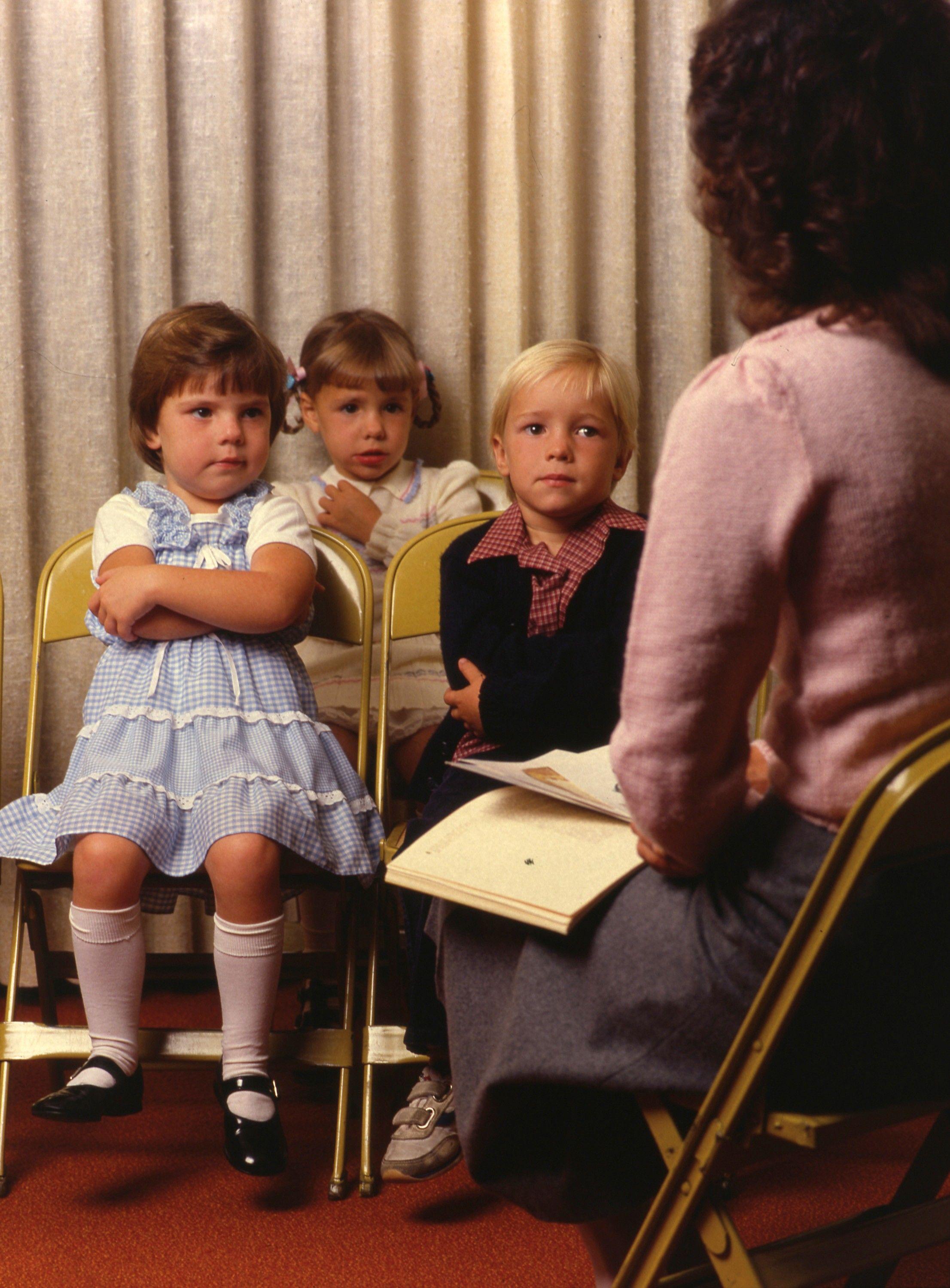 Three children sitting in a Primary class, listening to their teacher.