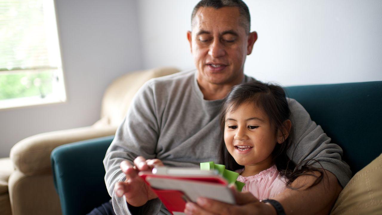 Uma menina e seu pai leem a Bíblia Sagrada em um tablet