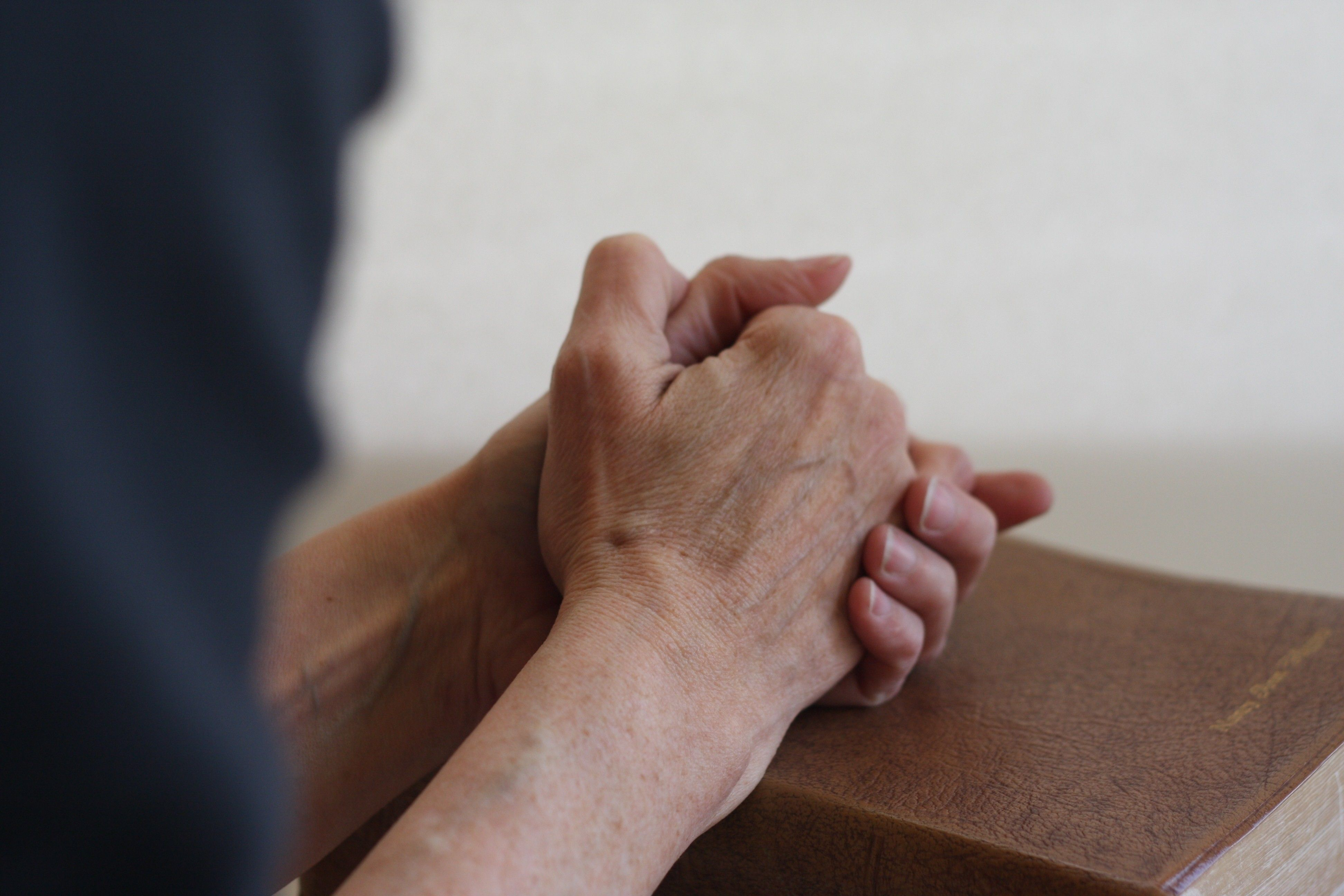 A person prays with clasped hands.