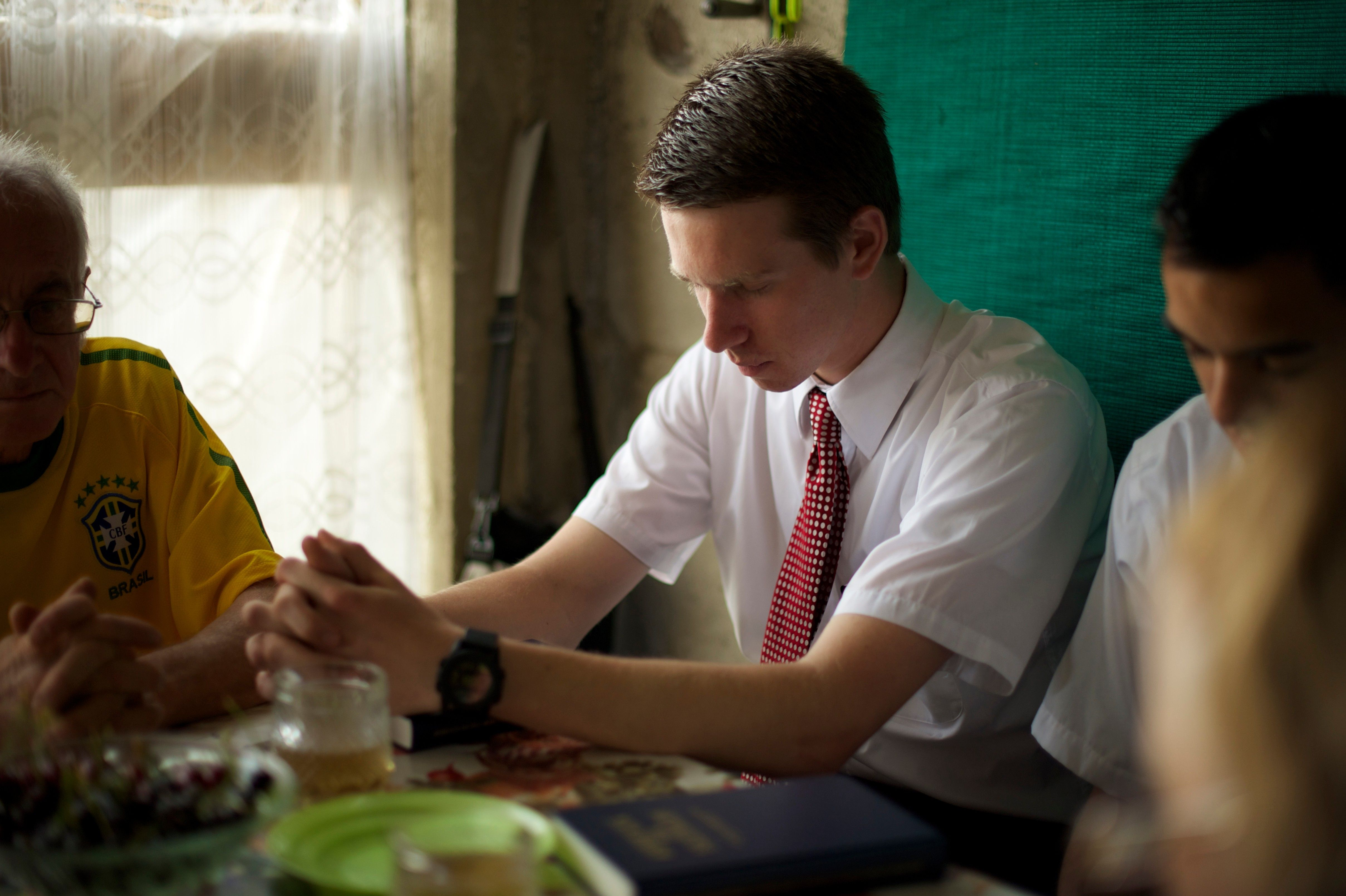 Missionaries pray at the dinner table.
