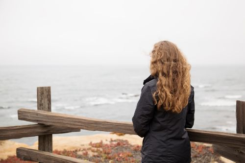 A young adult looking at the ocean