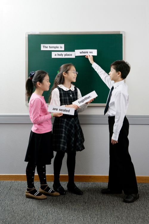 Primary children holding up word strips