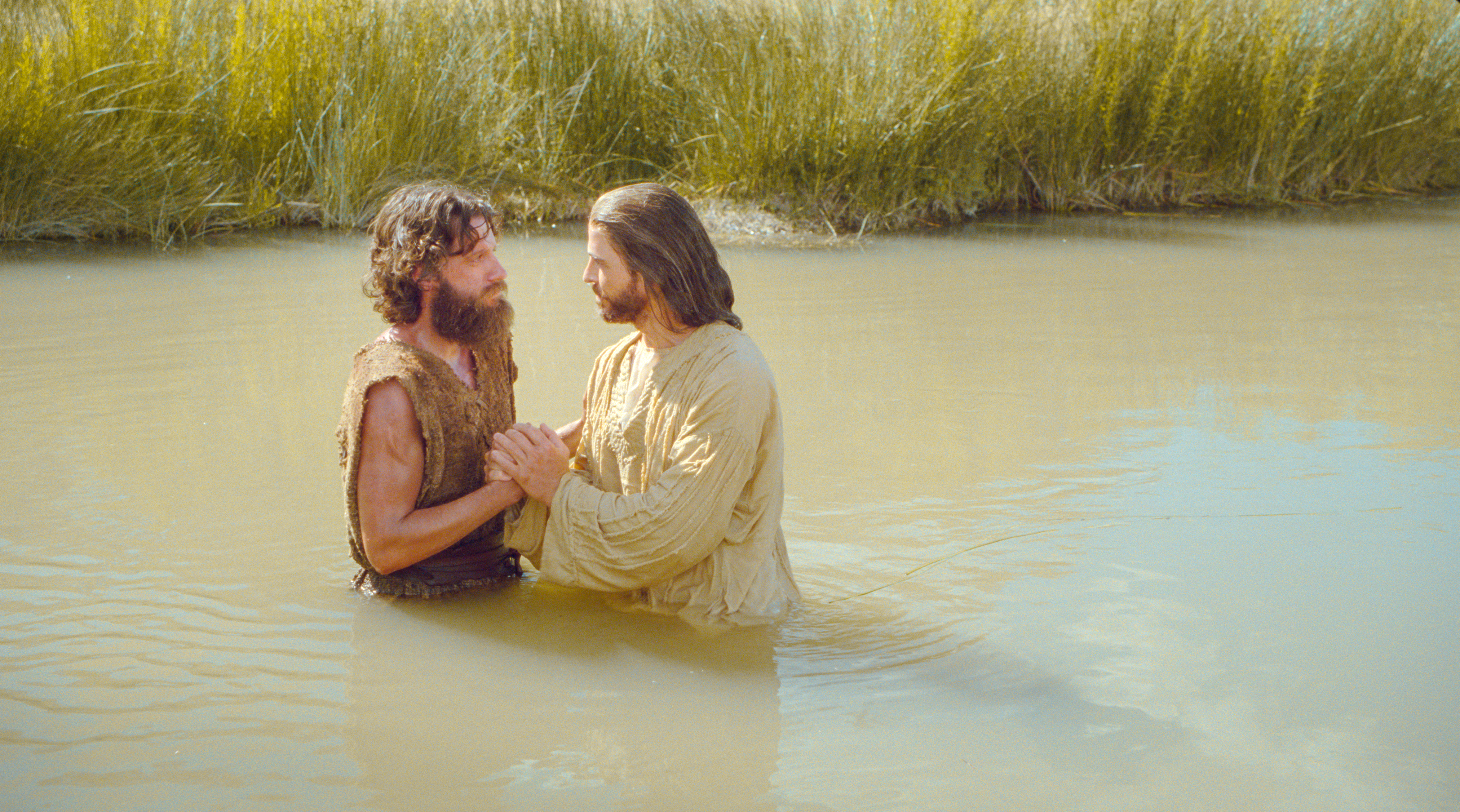 As Jesus enters the water to be baptized, John declares that he must be baptized by Jesus. Jesus responds that He must be baptized to fulfill all righteousness.