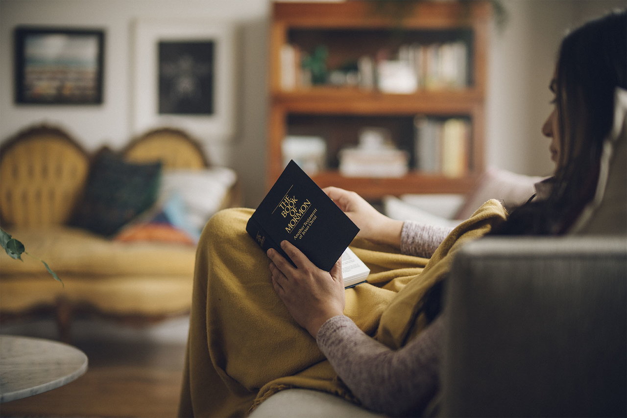 A girl reads the Book of Mormon on her couch