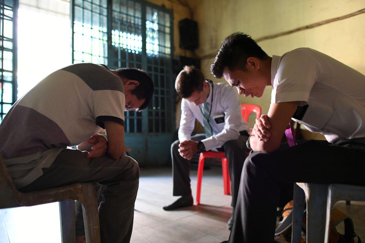 Un hombre ora con los misioneros