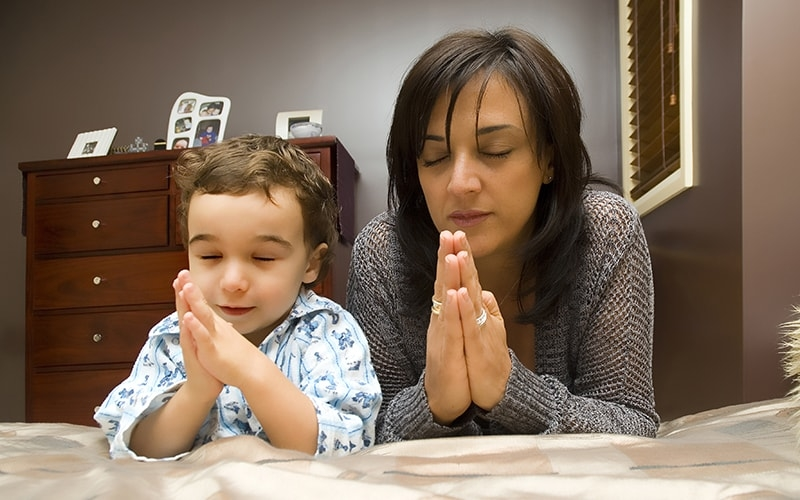 A mother teaches her child to pray at her bedside