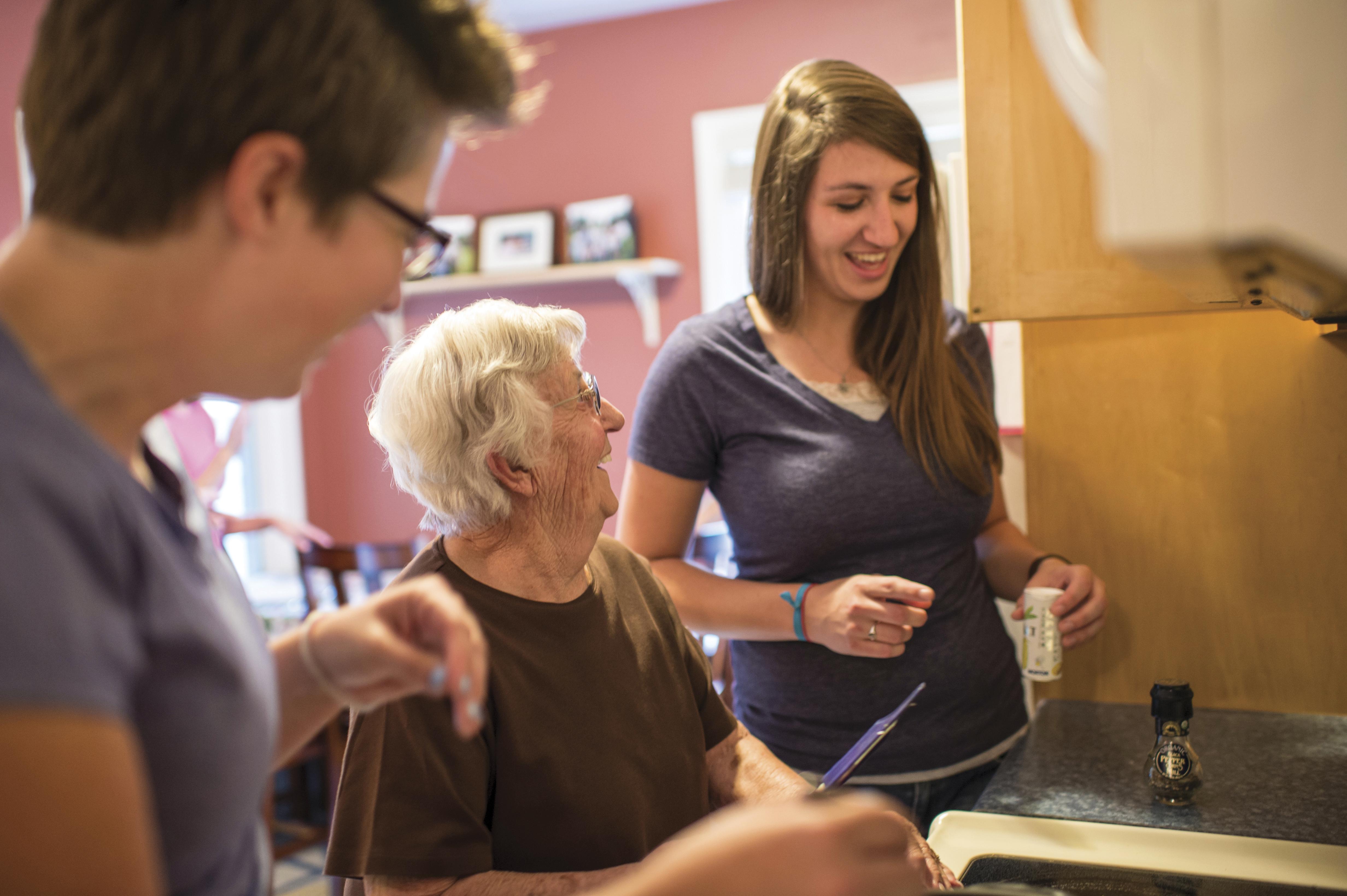 Young women helping an elderly woman.